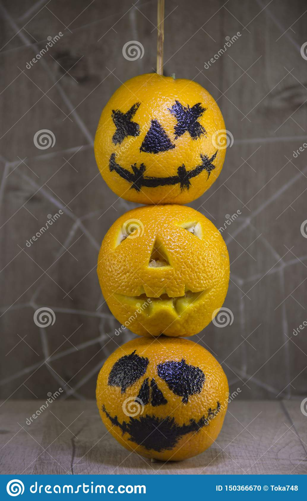 Jack lantern for Halloween of oranges on a wooden background with cobwebs