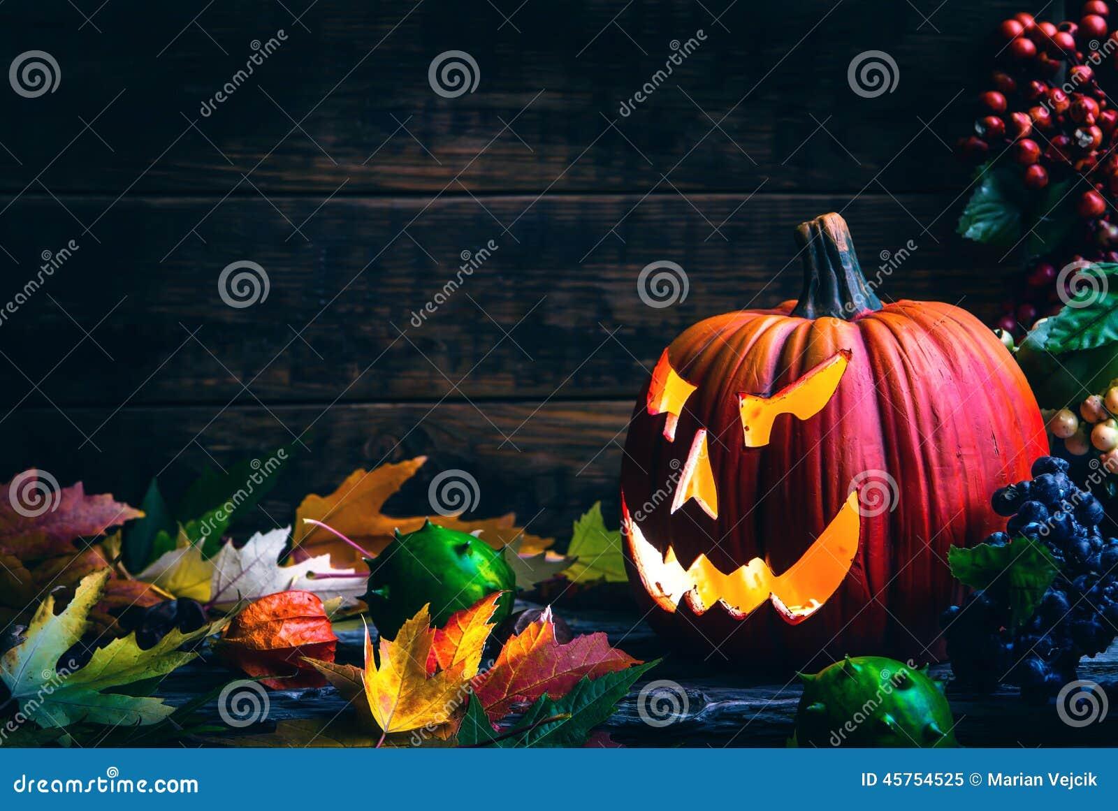 Jack o het de pompoengezicht van lantaarnshalloween op houten achtergrond en de herfst doorbladert