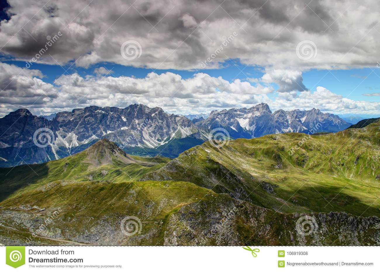 Jagged Sexten Dolomites with green slopes of Carnic Alps Italy