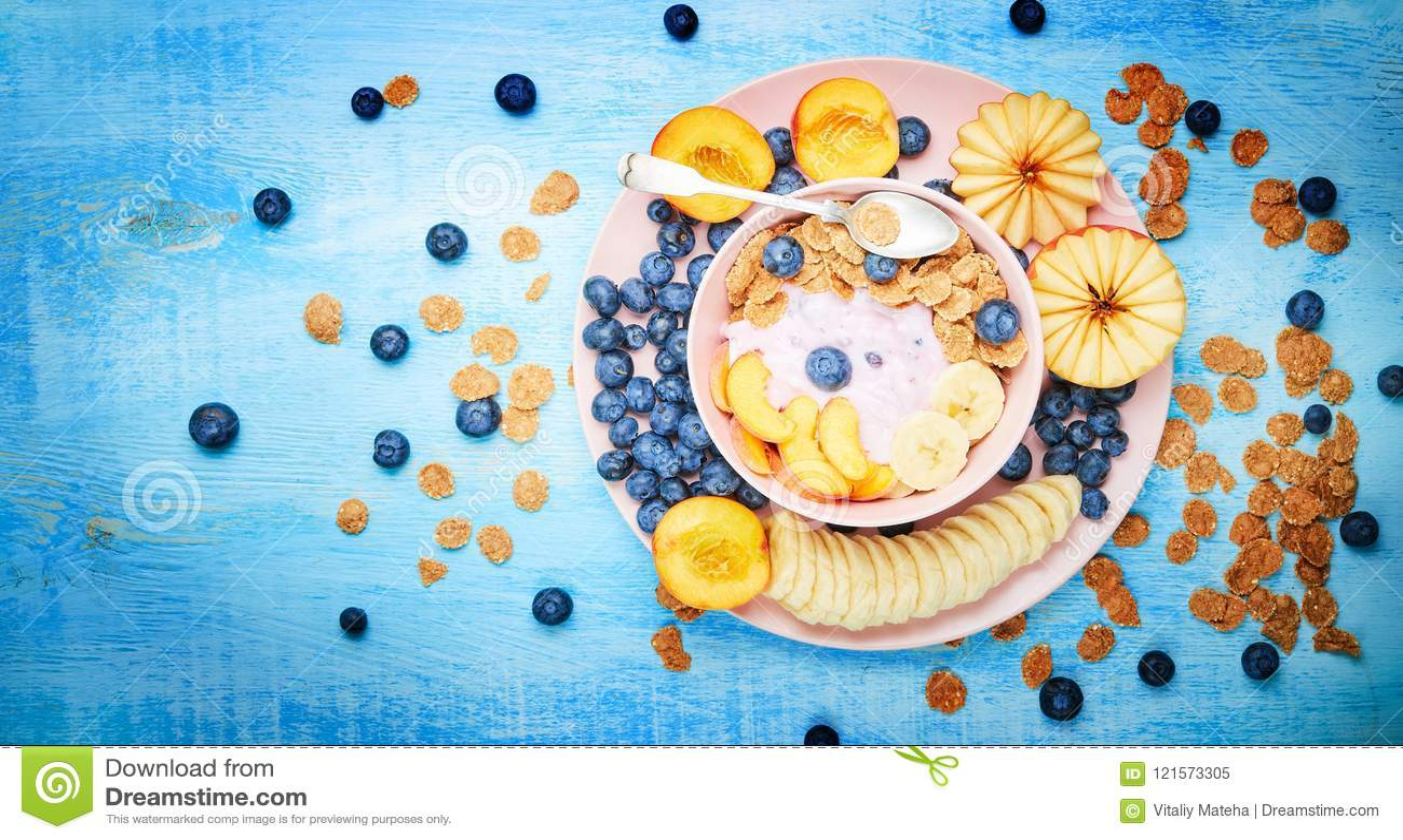 Jagodowy grecki jogurt z czarnymi jagodami, bananem i płatkami w różowym pucharze na błękitnym drewnianym stole frefh,