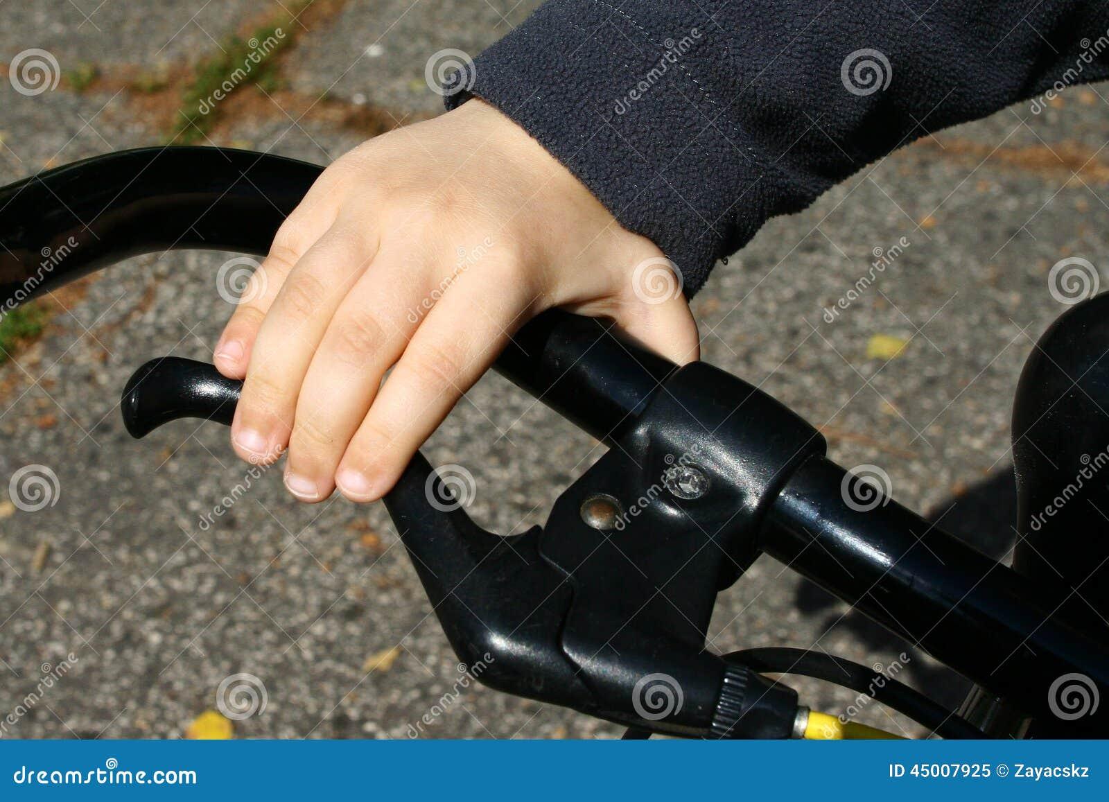 4 Jahre alte Jungenhand auf schwarzer Fahrradgriffbremse