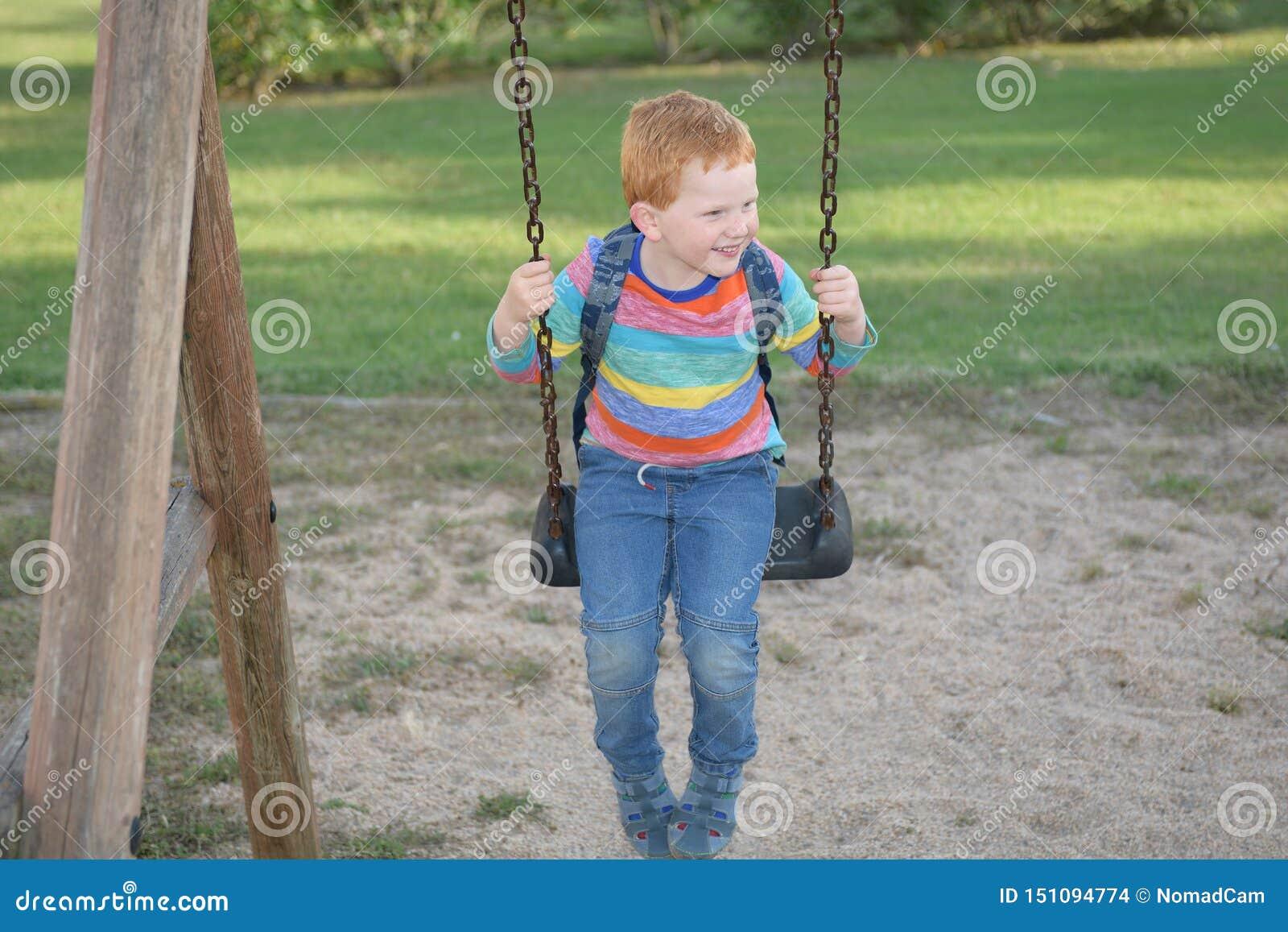 5 Jahre alte redheaded glückliche Junge mit seinem schwingenden und lächelnden Rucksack