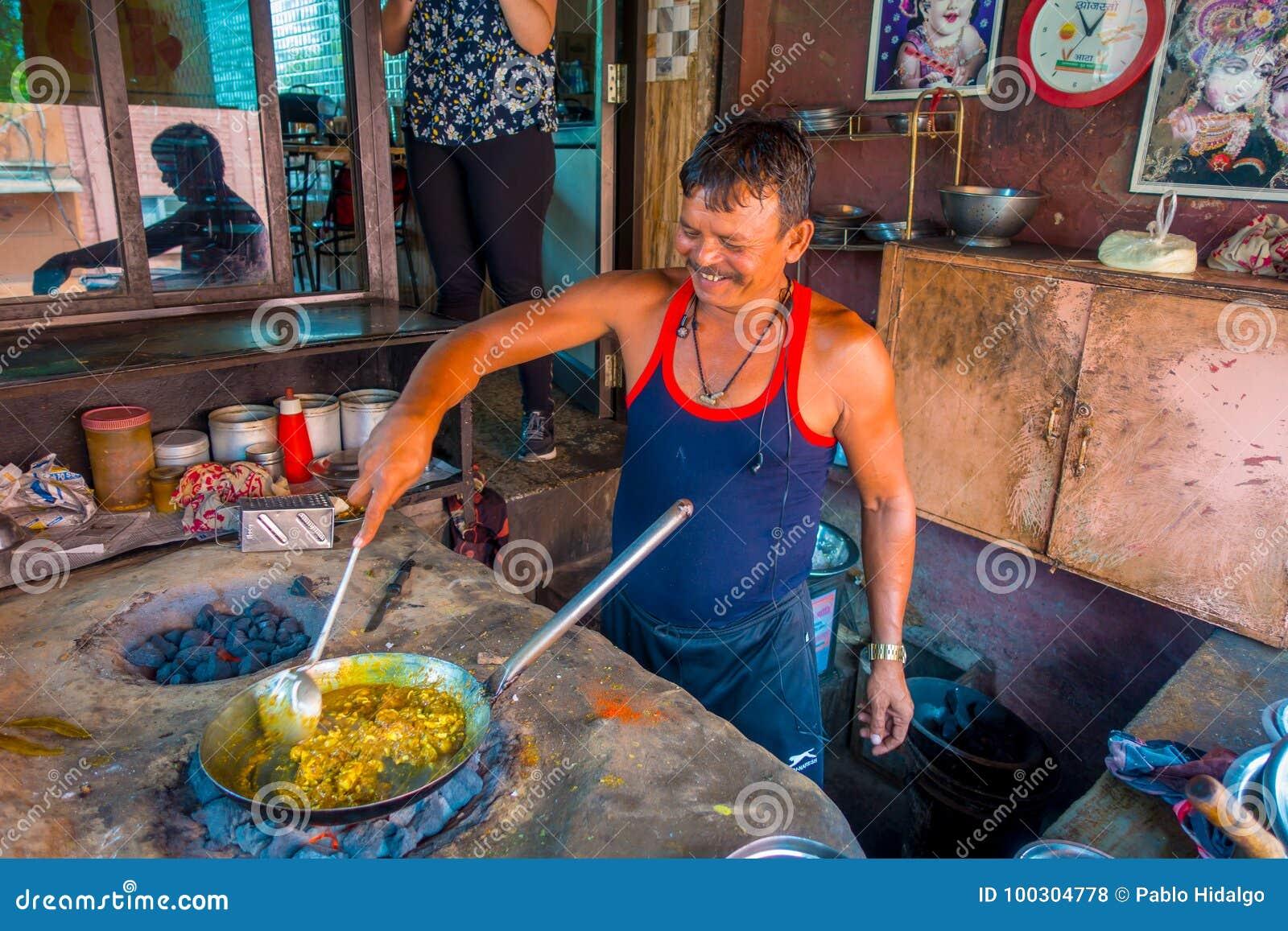 Jaipur, Índia - 20 de setembro de 2017: Homem não identificado que cozinha o alimento indiano em uma bandeja metálica sobre rocha