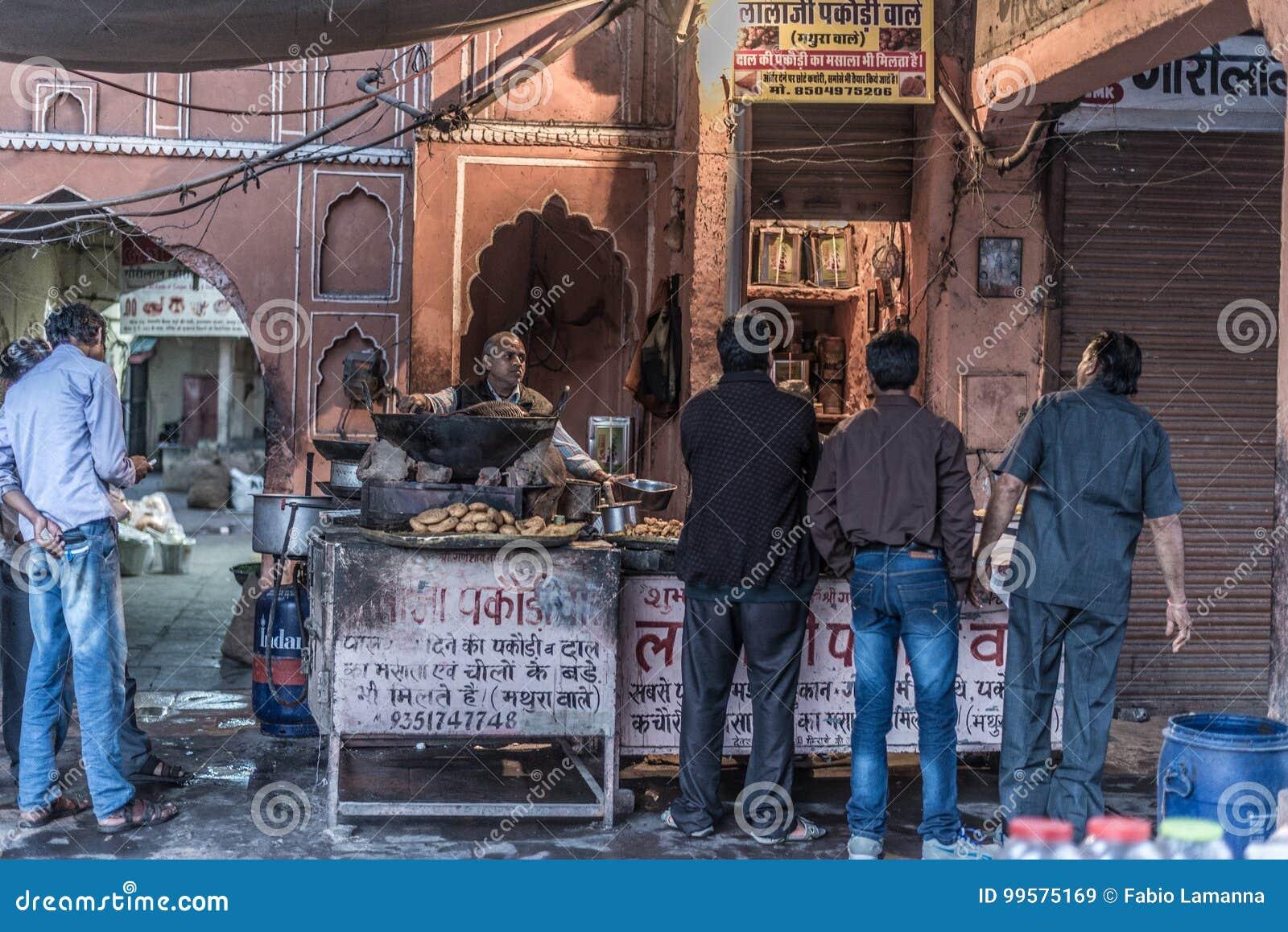 Jaipur Indien - Februari 5, 2017: matförsäljare och folk i en grungy gata på Jaipur, Rajasthan, berömd loppdestination i Ind