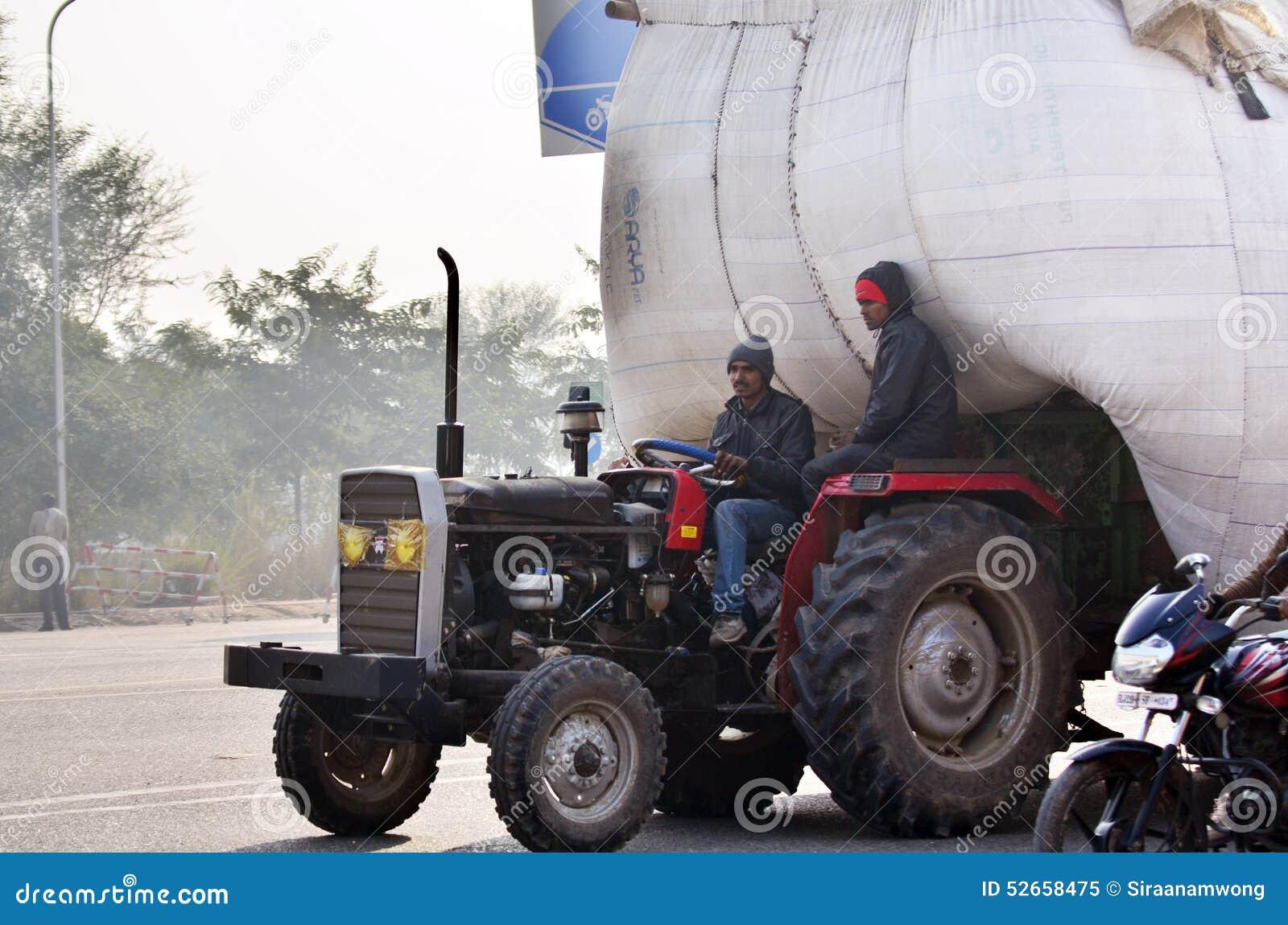 Jaipur, la India - 30 de diciembre de 2014: Hombre indio que conduce el camión pesadamente sobrecargado en Jaipur