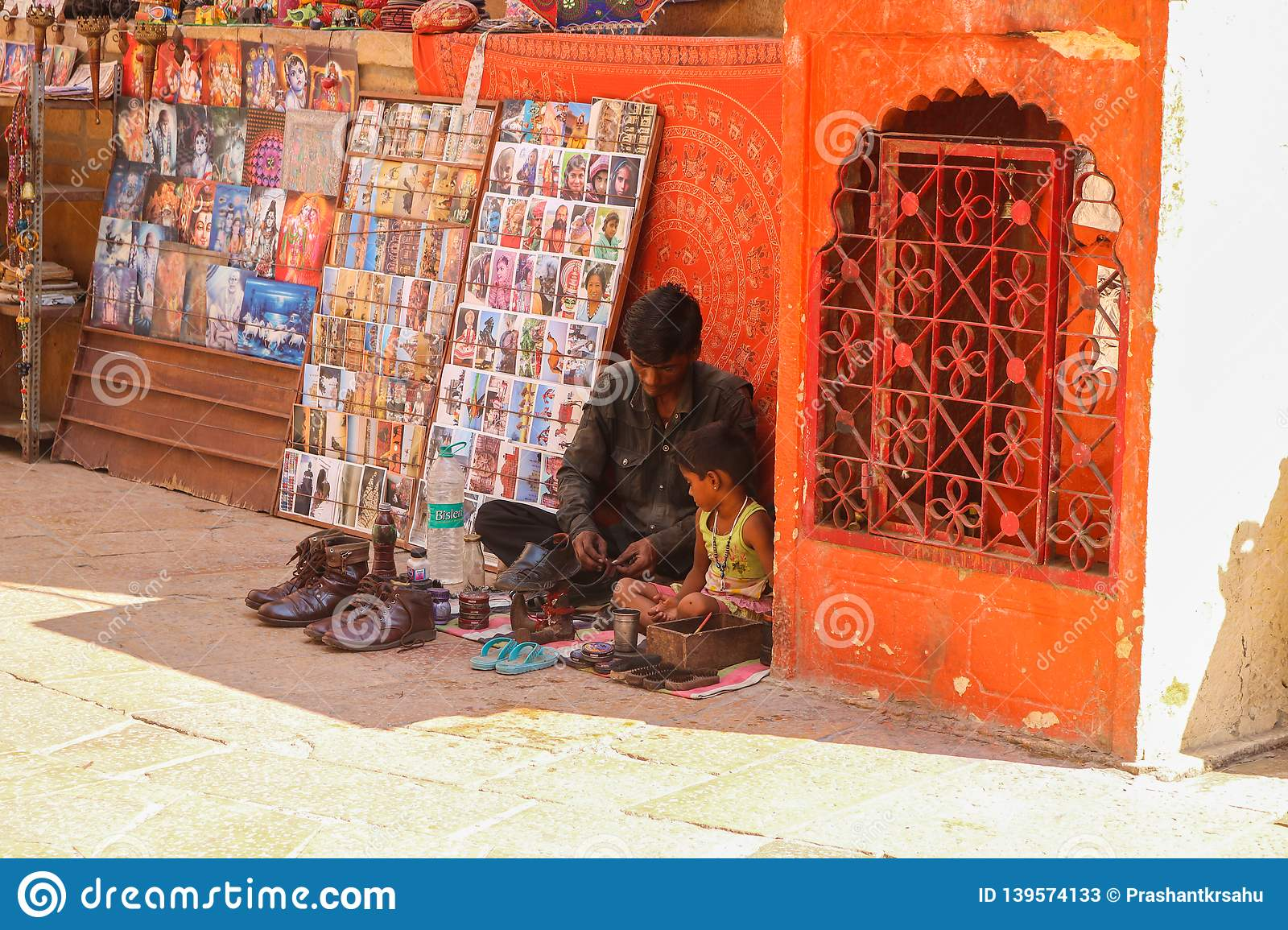 Shoemaker with his child setting at the street of Jaisalmer