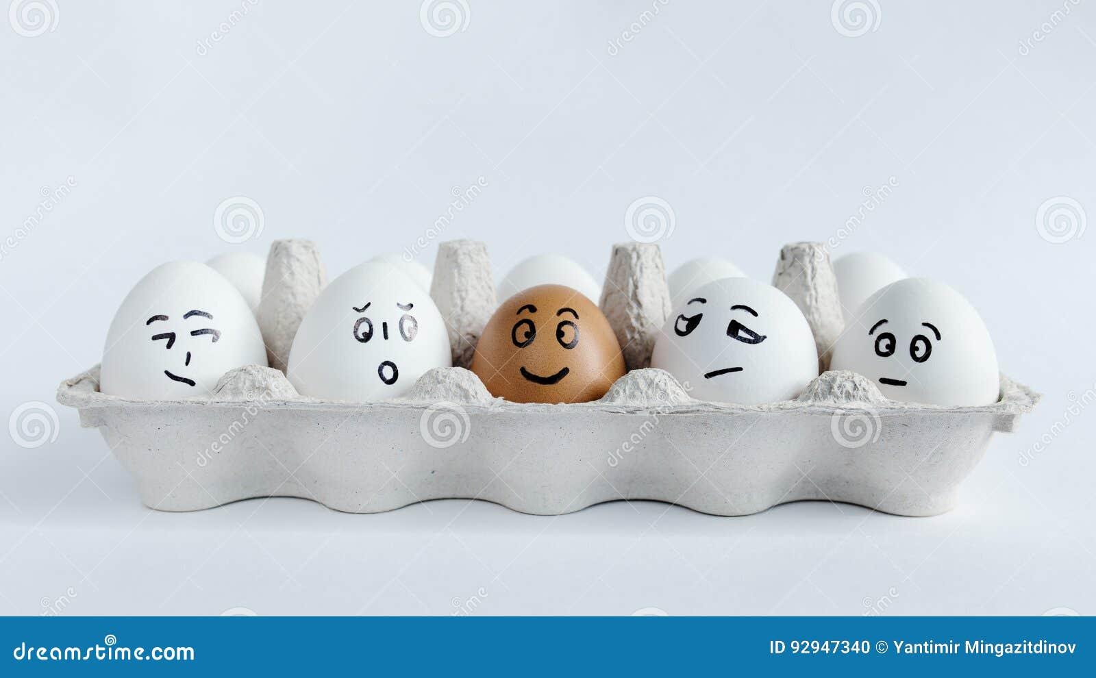 Jajka z śmiesznymi twarzami w pakunku na białym tle Wielkanocna pojęcie fotografia Twarze na jajkach