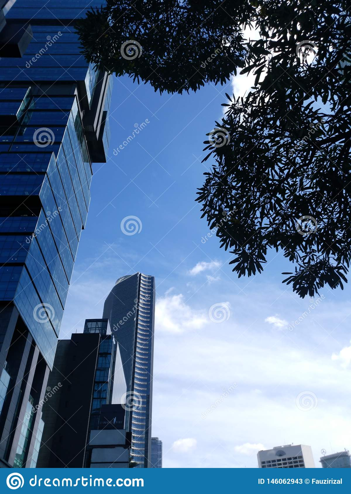 Jakarta building view in the City. Morning Blue sky and many clouds with tree as the foreground