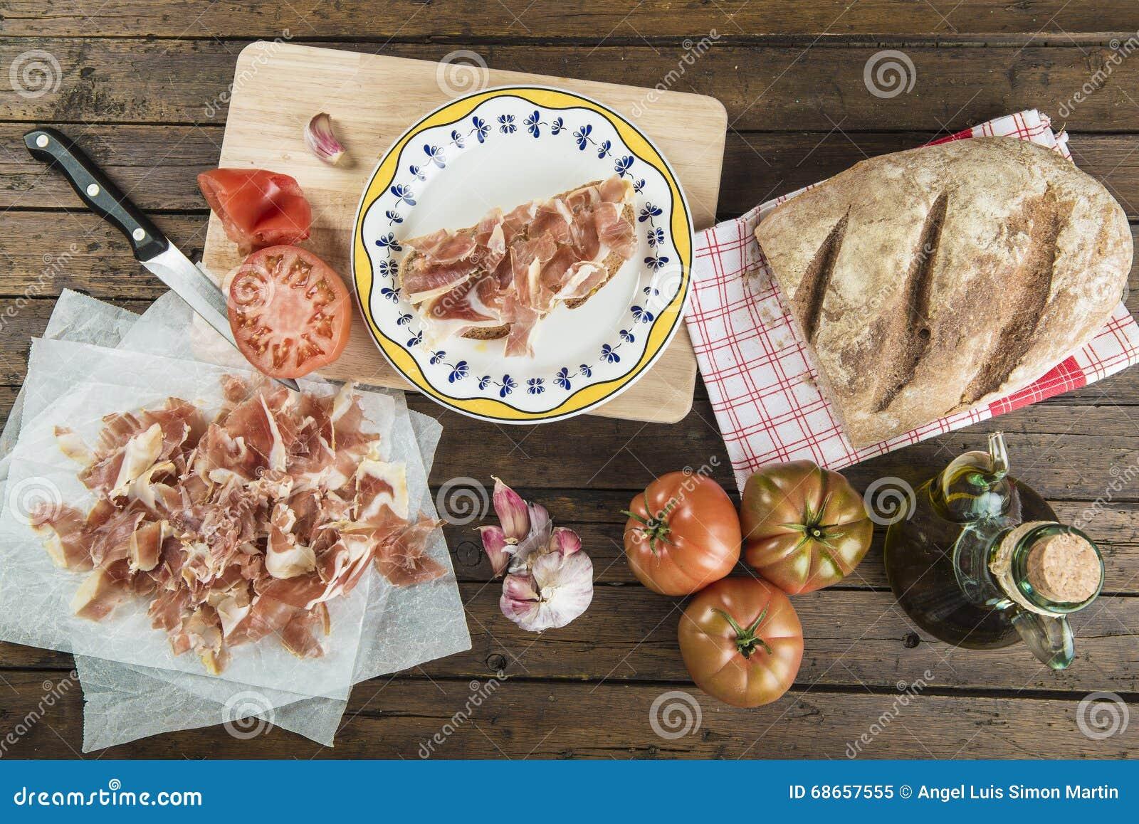 Jamón con pan, el tomate, el ajo y el aceite de oliva
