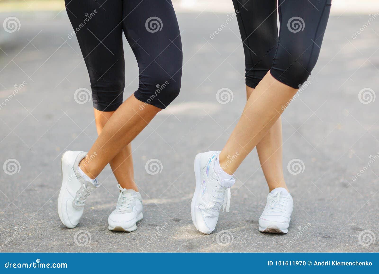 Jambes convenables de plan rapproché dans les vêtements de sport sur un fond brouillé Filles dans des espadrilles Concept de cour