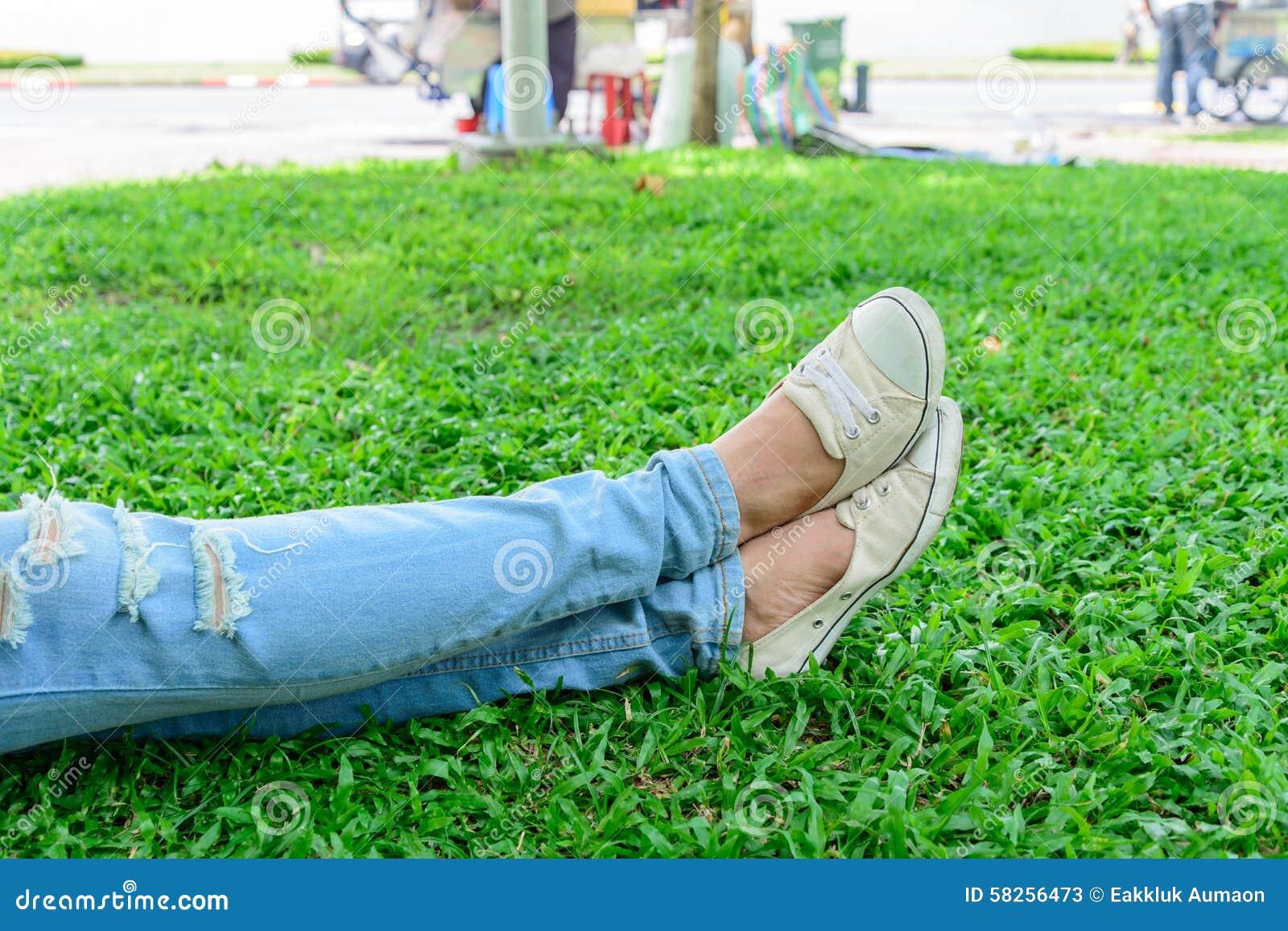 Jambes cultivées de femme en denim avec les espadrilles blanches se reposant sur l herbe