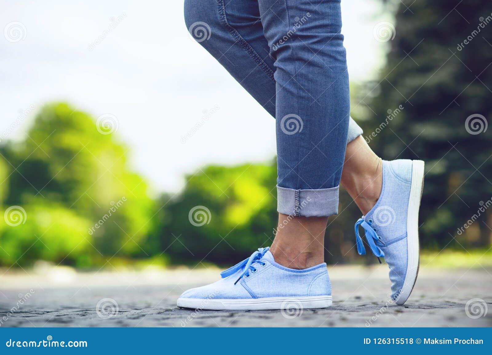 Jambes d une fille dans les jeans et des espadrilles bleues sur une tuile de trottoir, une jeune femme flânant en parc d été
