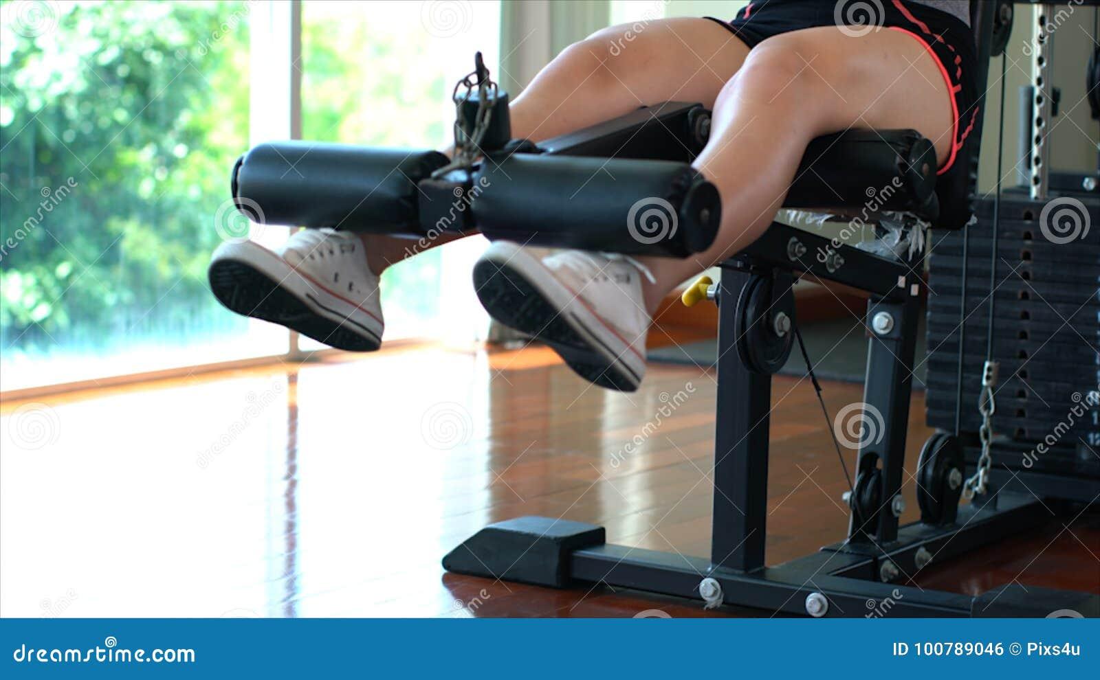 Jambes de la jeune fille de sport faisant les boucles de jambe posées sur la machine en GY