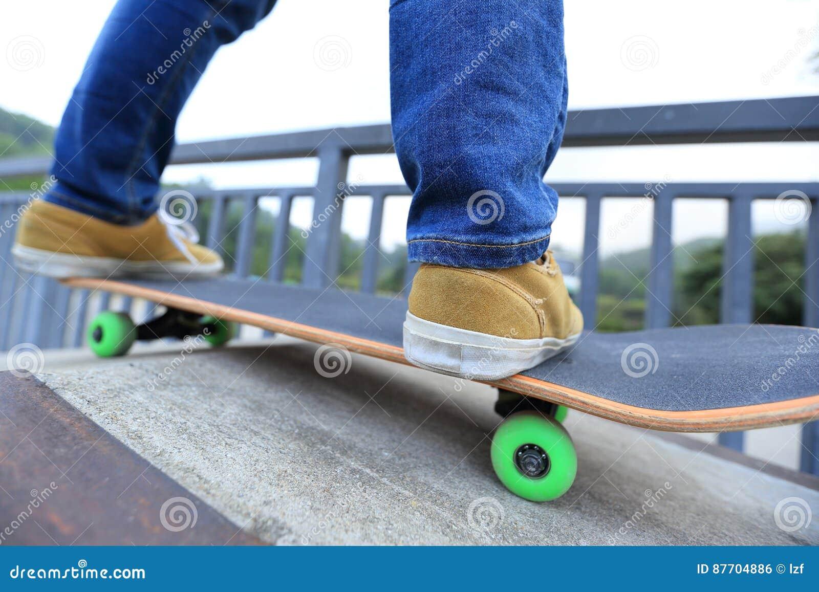 Jambes de planchiste montant la planche à roulettes au skatepark