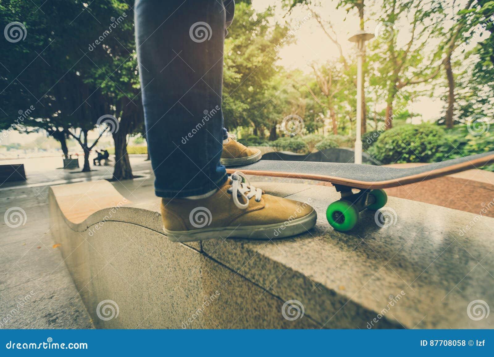 Jambes de planchiste montant la planche à roulettes au skatepark de ville