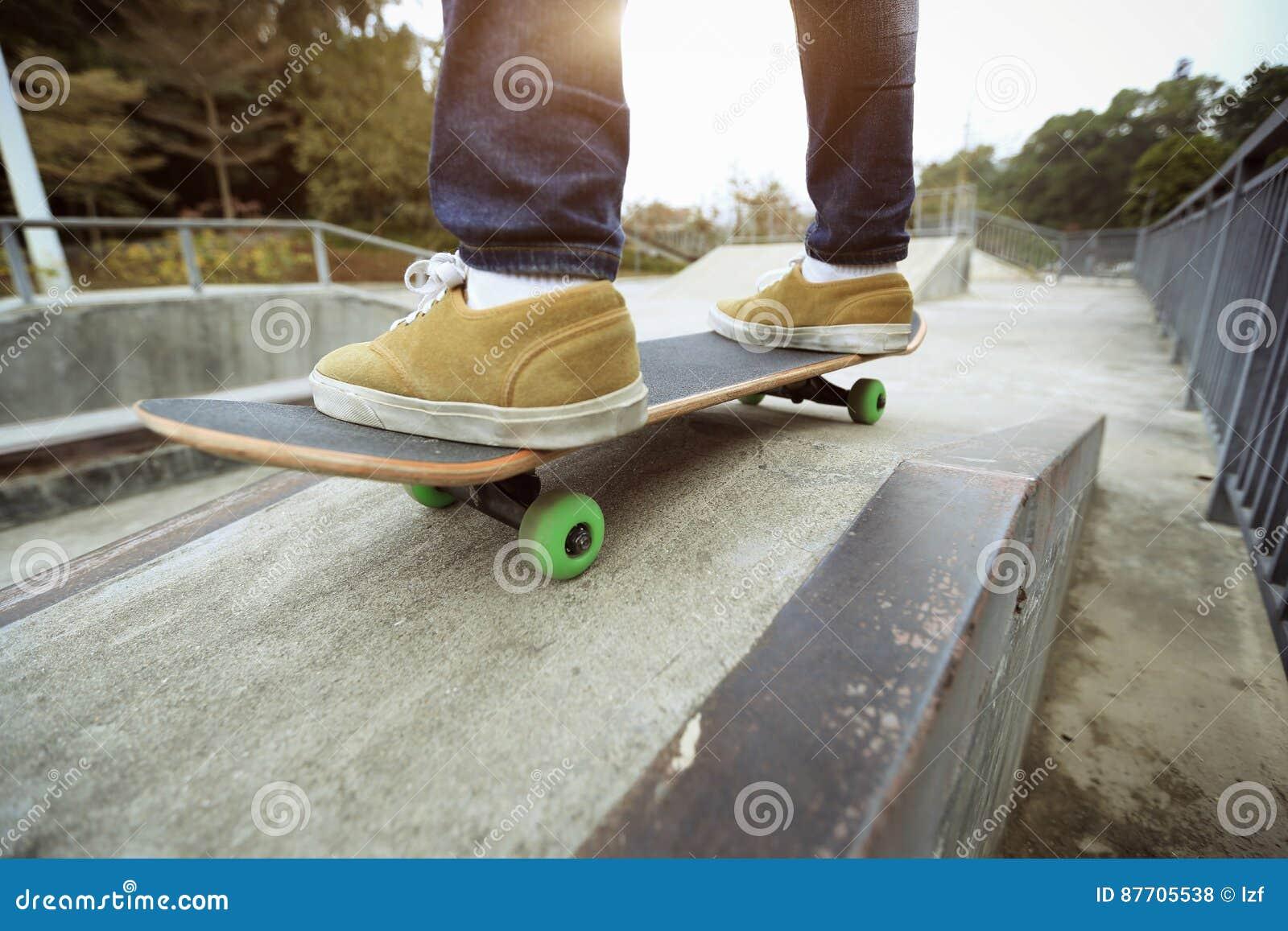 Jambes de planchiste montant la planche à roulettes à la rampe de skatepark