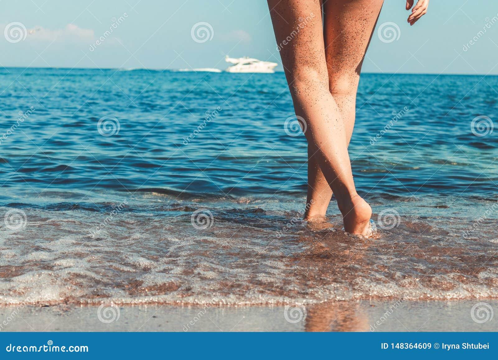 Jambes sexy du ` s de femmes belles sur la plage