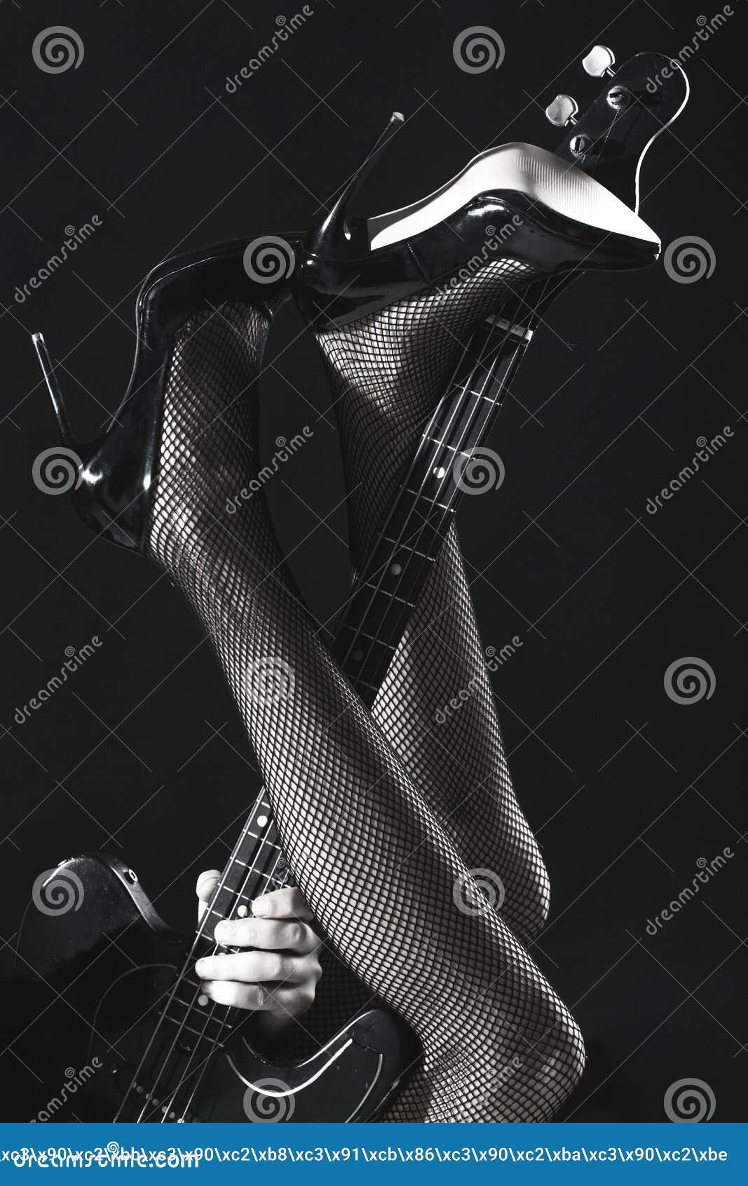 Jambes sexy, longues jambes sur des talons hauts, chaussures Instrument sur l étape et la bande La guitare électrique, basse-guit