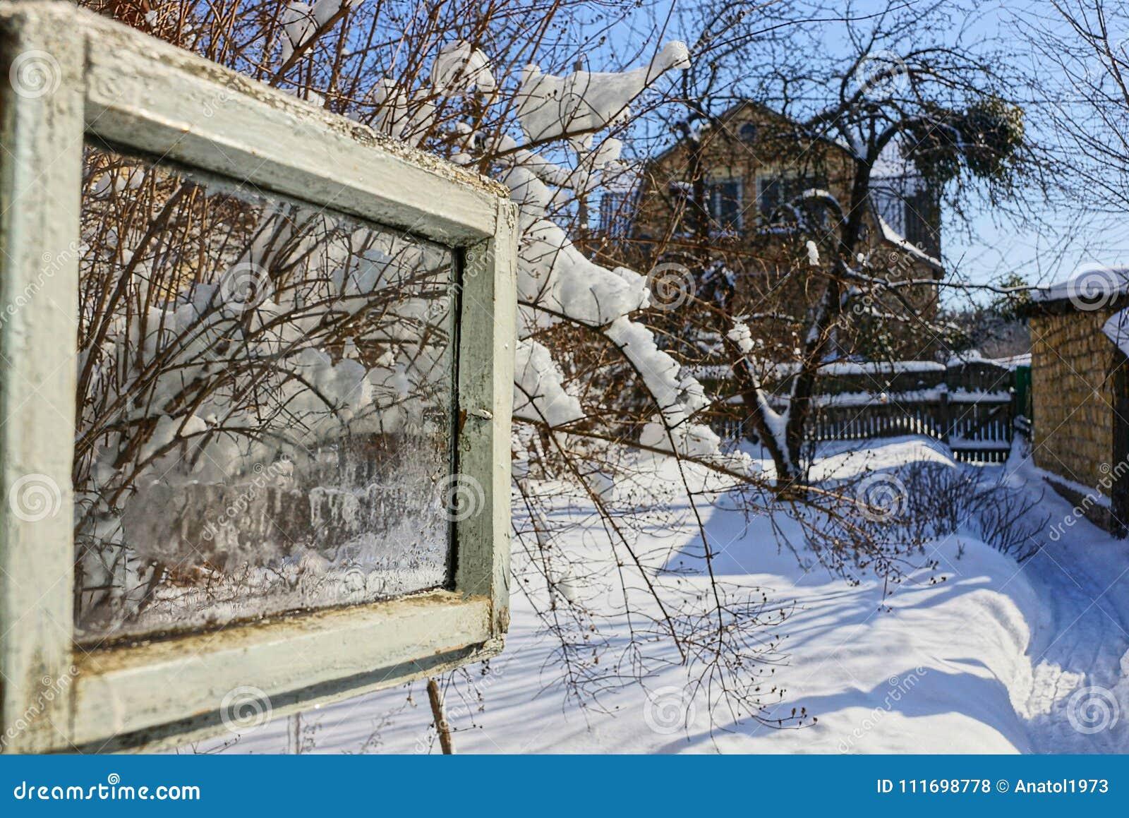 Janela aberta com uma vista da rua do inverno
