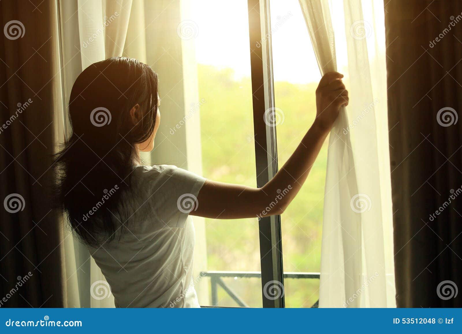 Janela aberta da jovem mulher