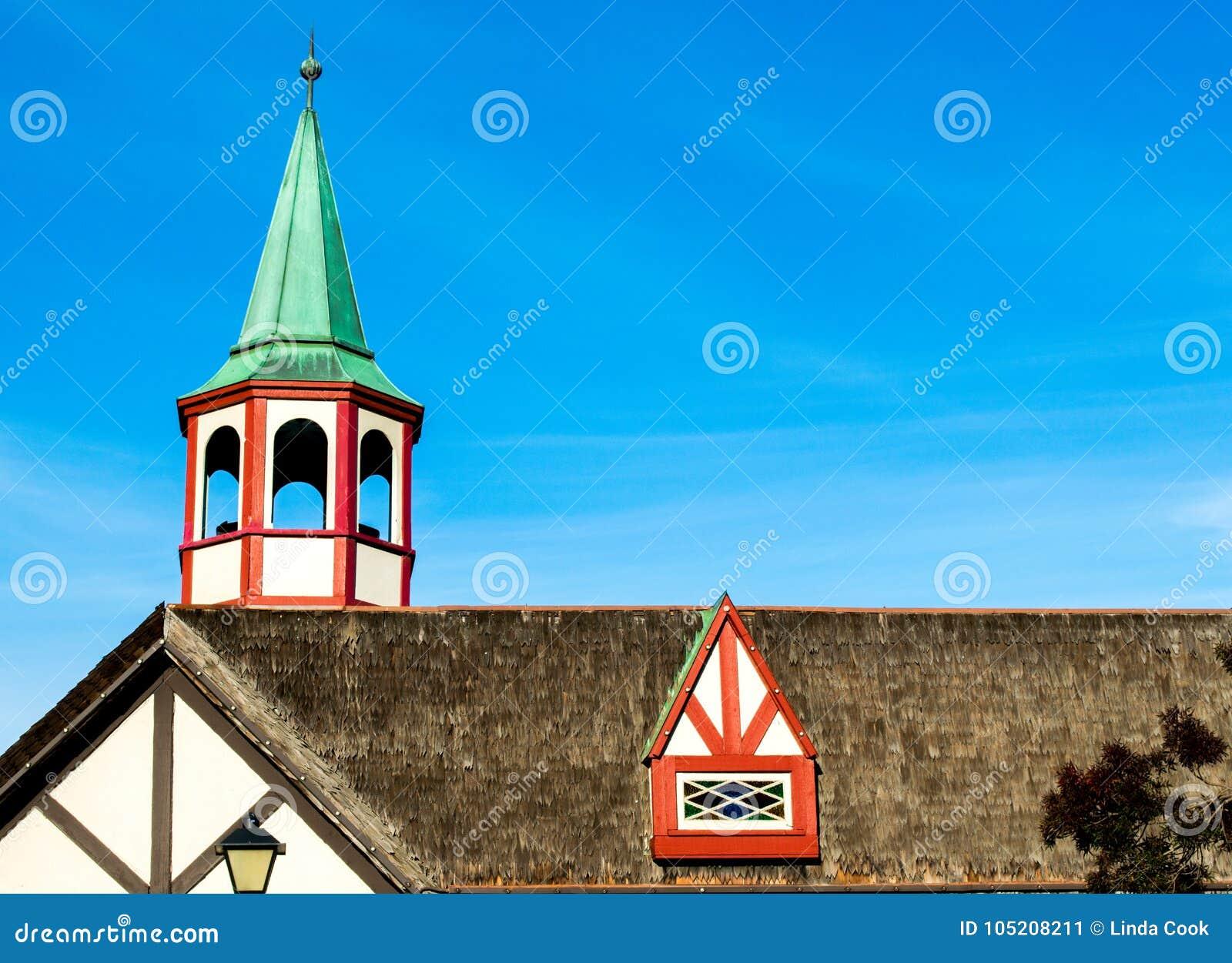 Janela colorida da torre e de trapeira no telhado cobrido com sapê
