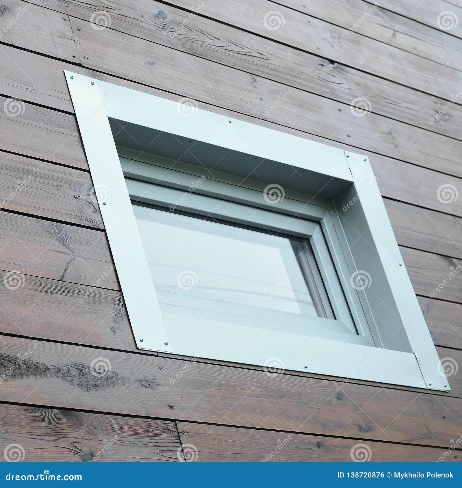 Janela plástica do PVC na parede de madeira passiva moderna nova da fachada da casa
