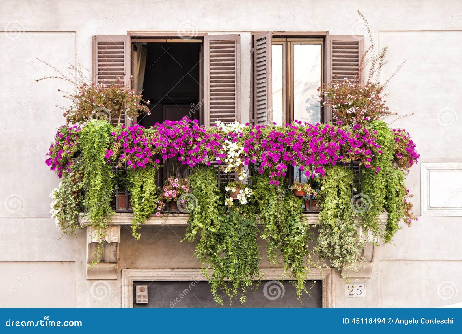 Janelas italianas do balcão completamente das plantas e das flores