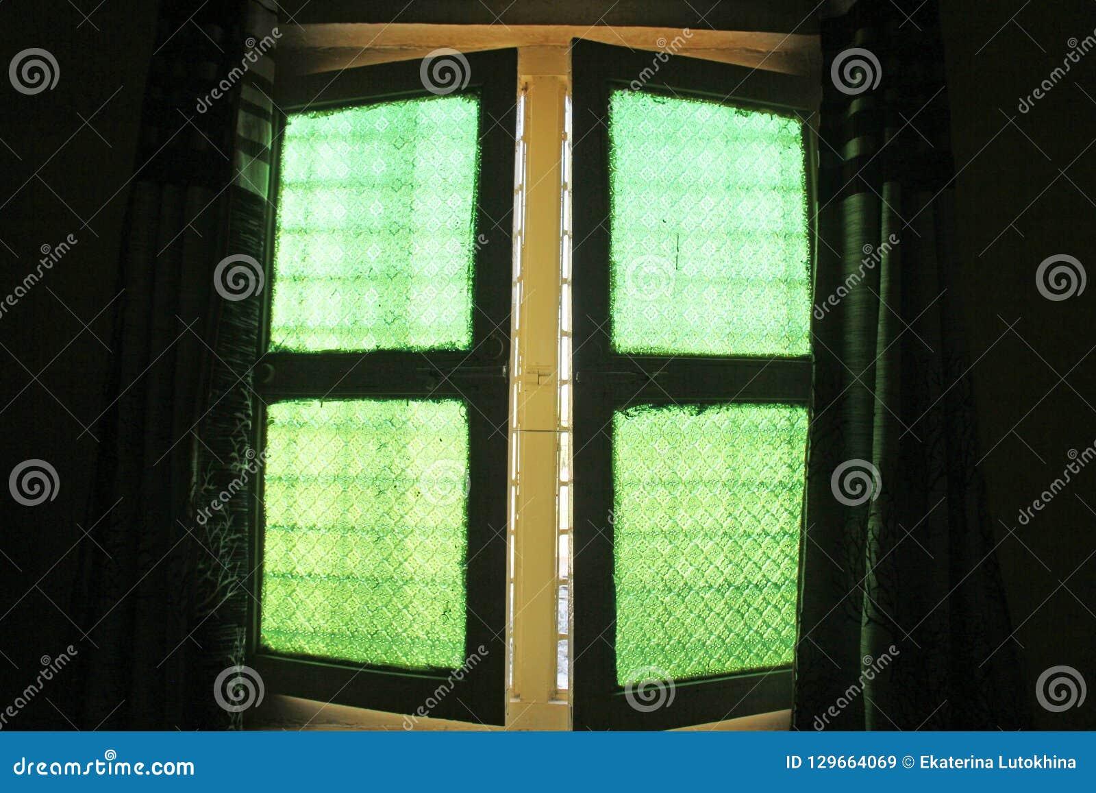 Janelas verdes do vidro velho do vintage com pa floral ou geométrico