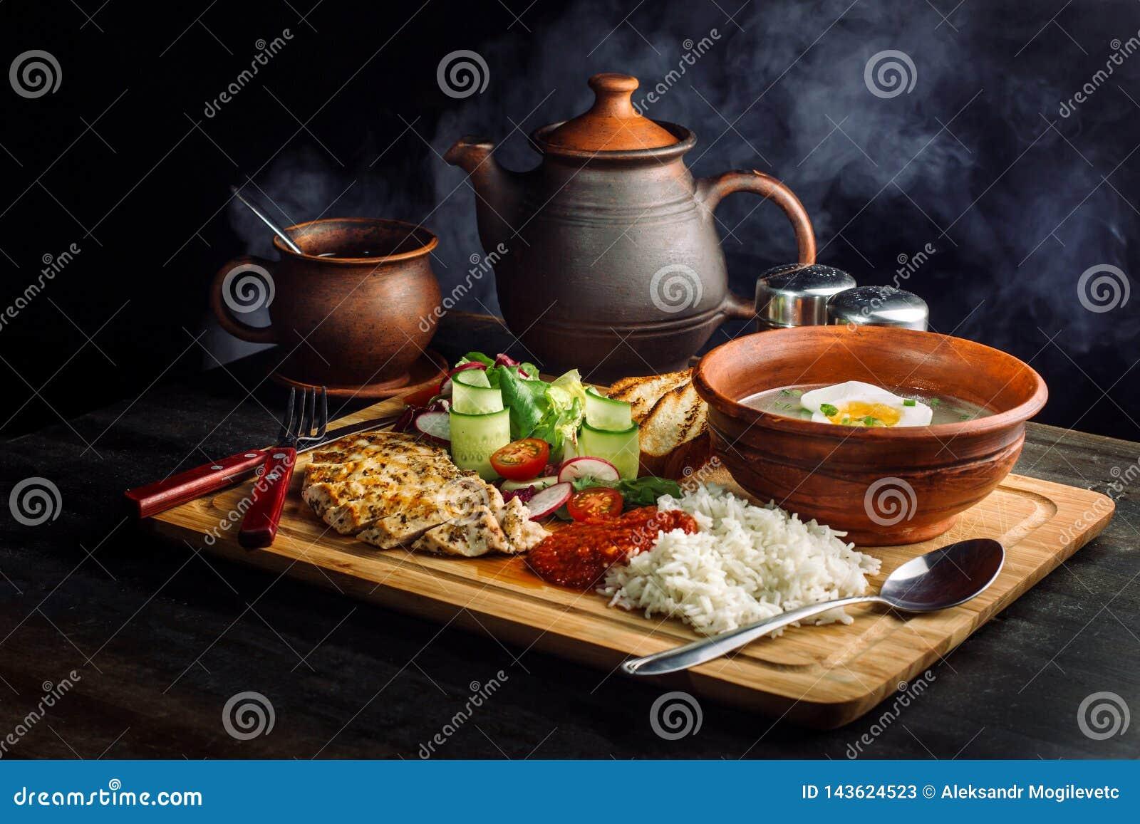 Jantar colocado na sopa da tabela, da cebola e do ovo, arroz, peito de frango