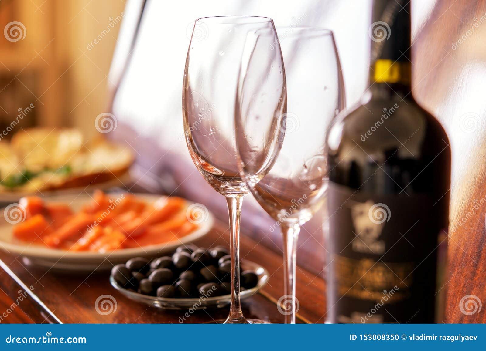 Jantar e vinho tinto românticos os pratos estão no piano: peixes, azeitonas, vidros