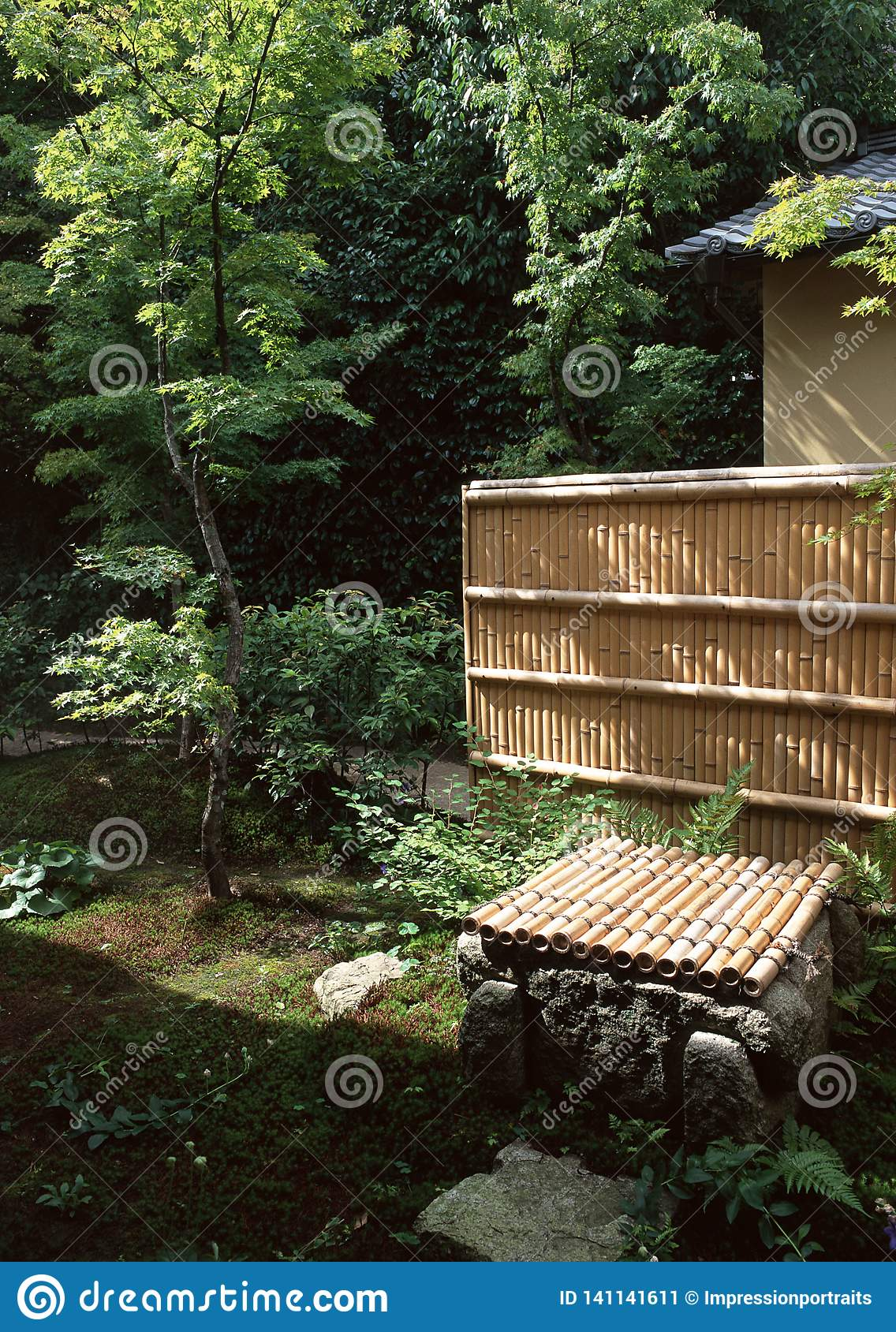 Japanese bamboo wall in outdoor garden with trees and plants
