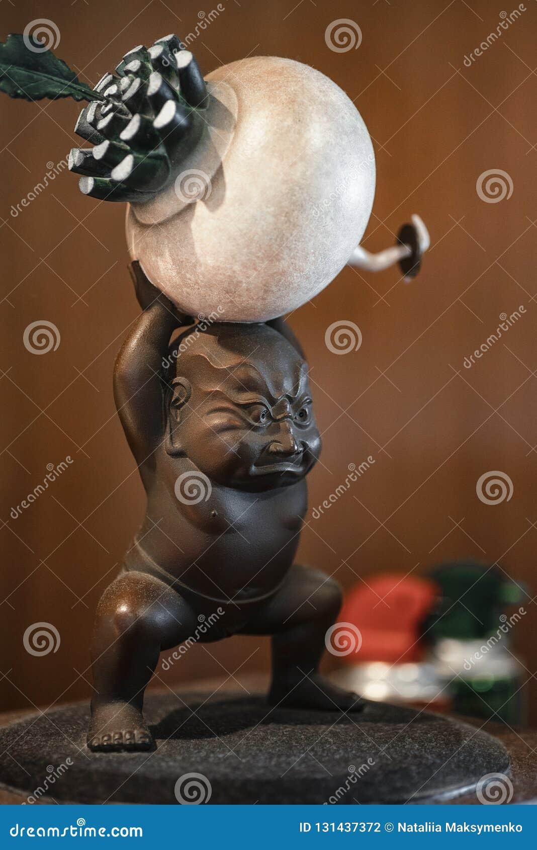Japanese ceramic statuette symbol. Japanese ceramic figurine of a man with a radish.The figurine souvenir.background