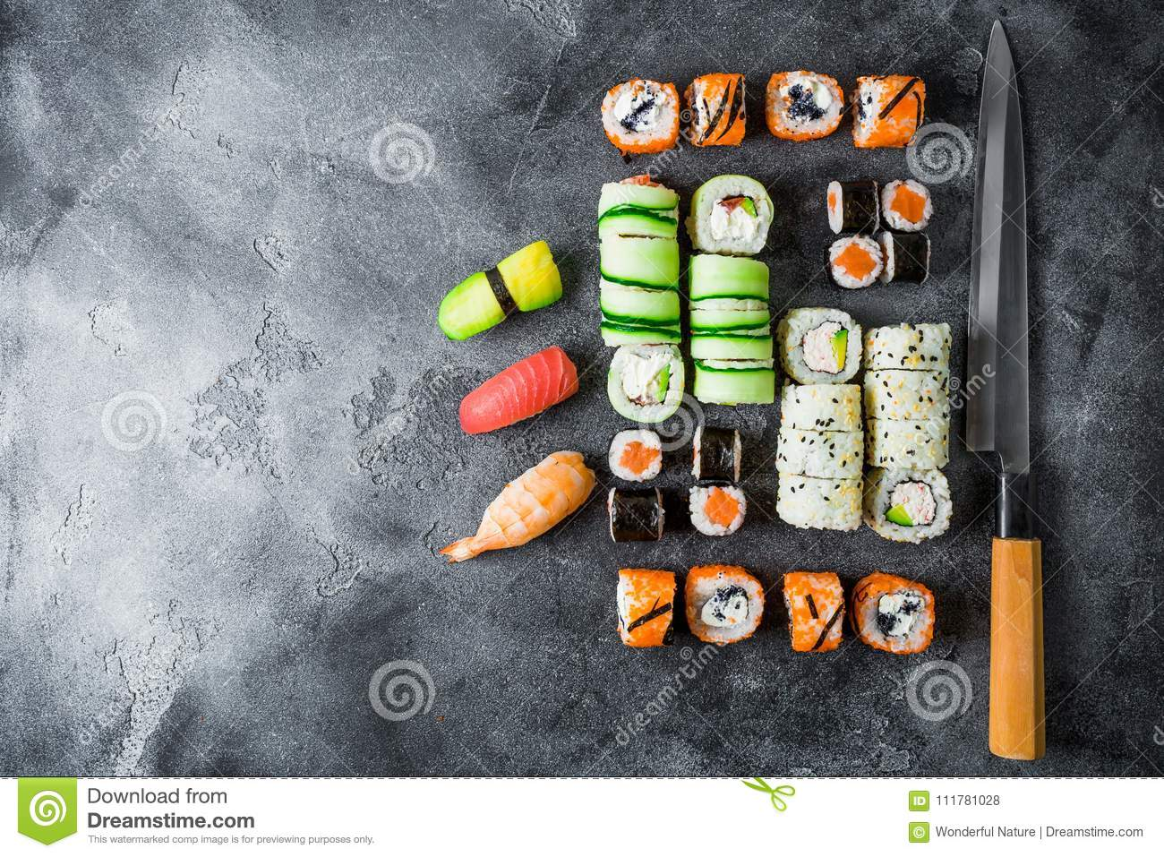 Japanese food concept with sushi, rolls and knife on dark background. Flat lay, Top view