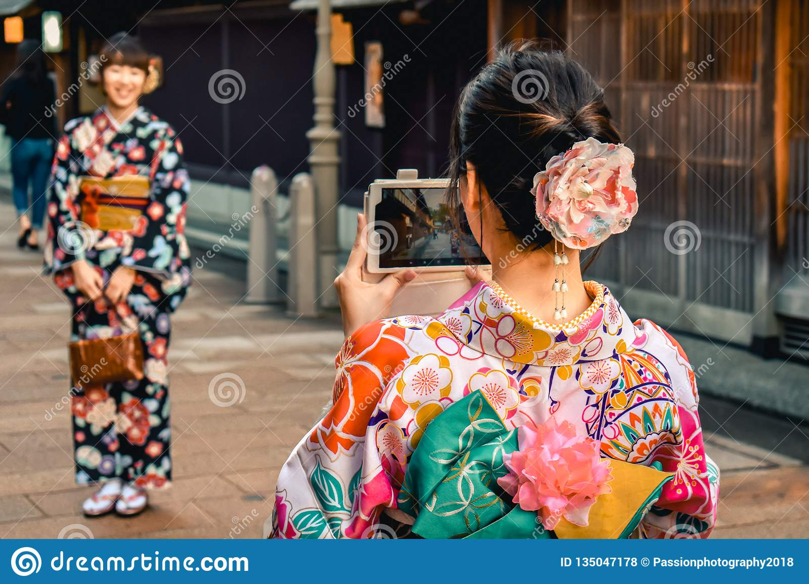 Japanese girls in Kimono`s taking photos of each other on a cell phone in the Kanazawa old town