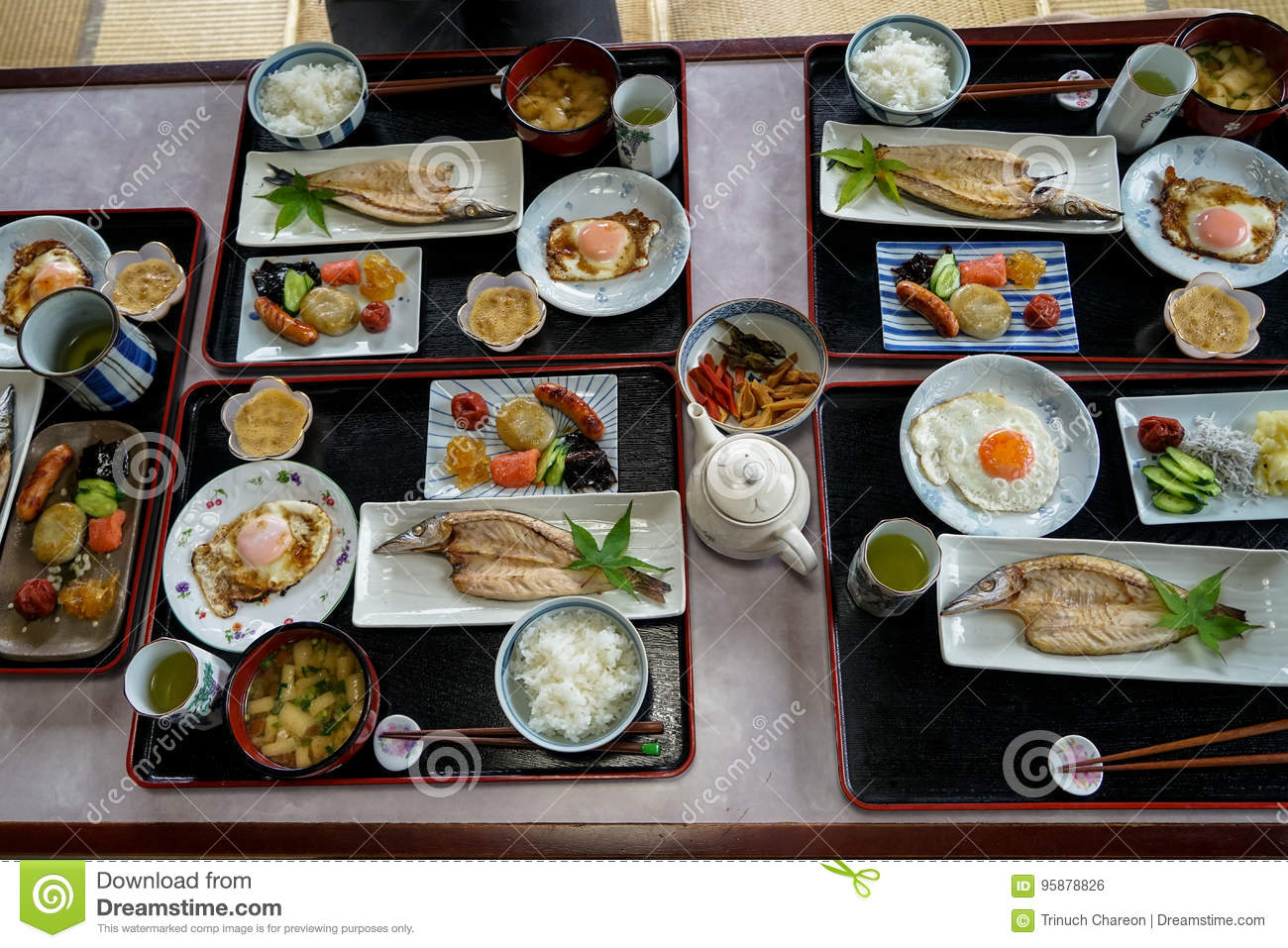 Japanese homestay breakfast tray including cooked white rice, grilled fish, fried egg, tofu soup, sausage, pickle, seaweed, etc.