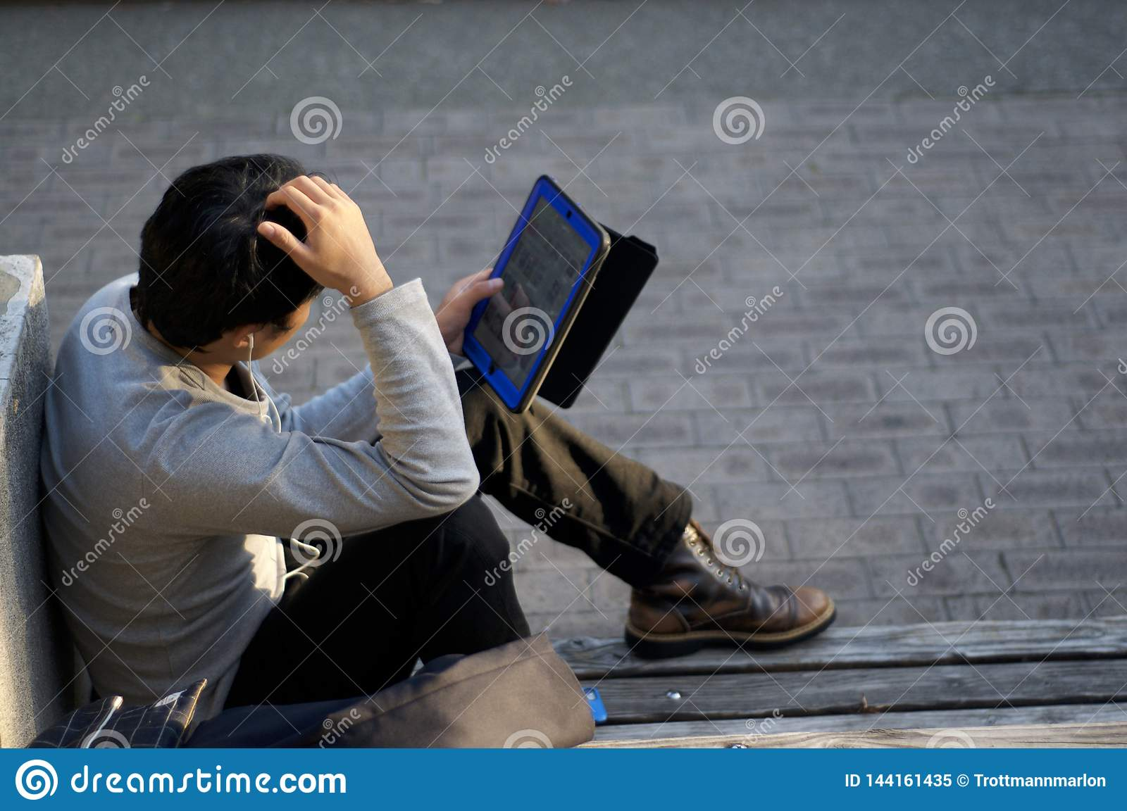 Japanese man is enjoying his tablet on a bench at Kobe`s East Park Higashi Yuenchi in Japan