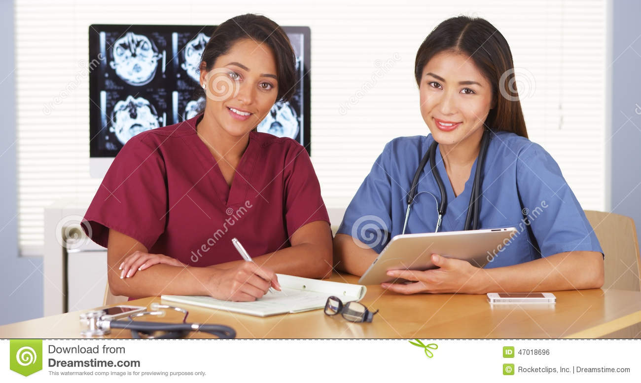 Japanese and Mexican medical doctors smiling at desk