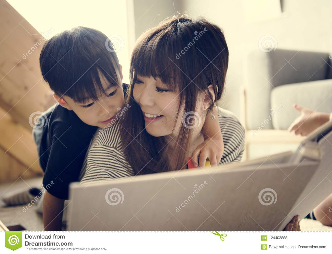 Japanese mother and son watching family photo album in living room
