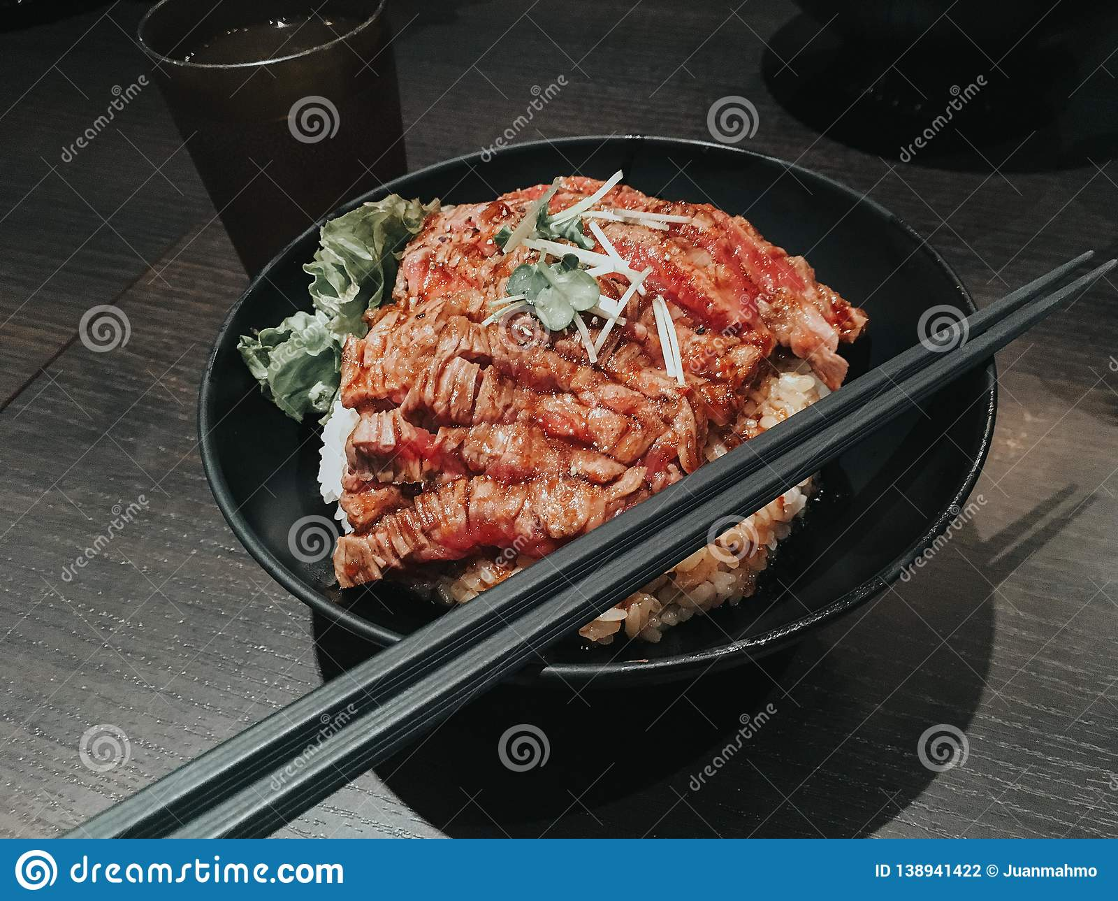 Japanese steak rice bowl. A steak is a meat generally sliced across the muscle fibers, potentially including a bone. Exceptions,