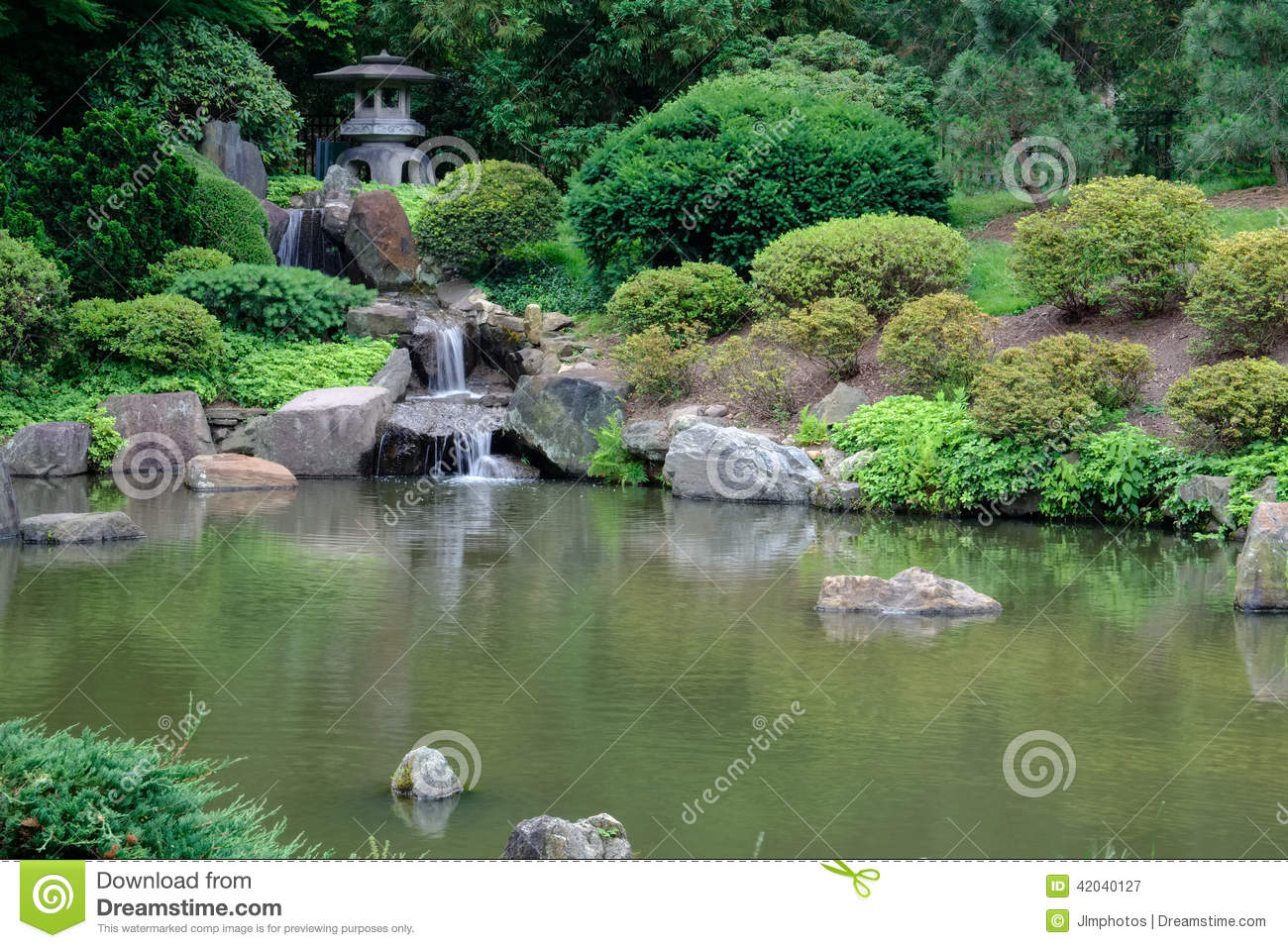 Japanese stone lanterns and waterfall into the koi fish for Stone koi pond