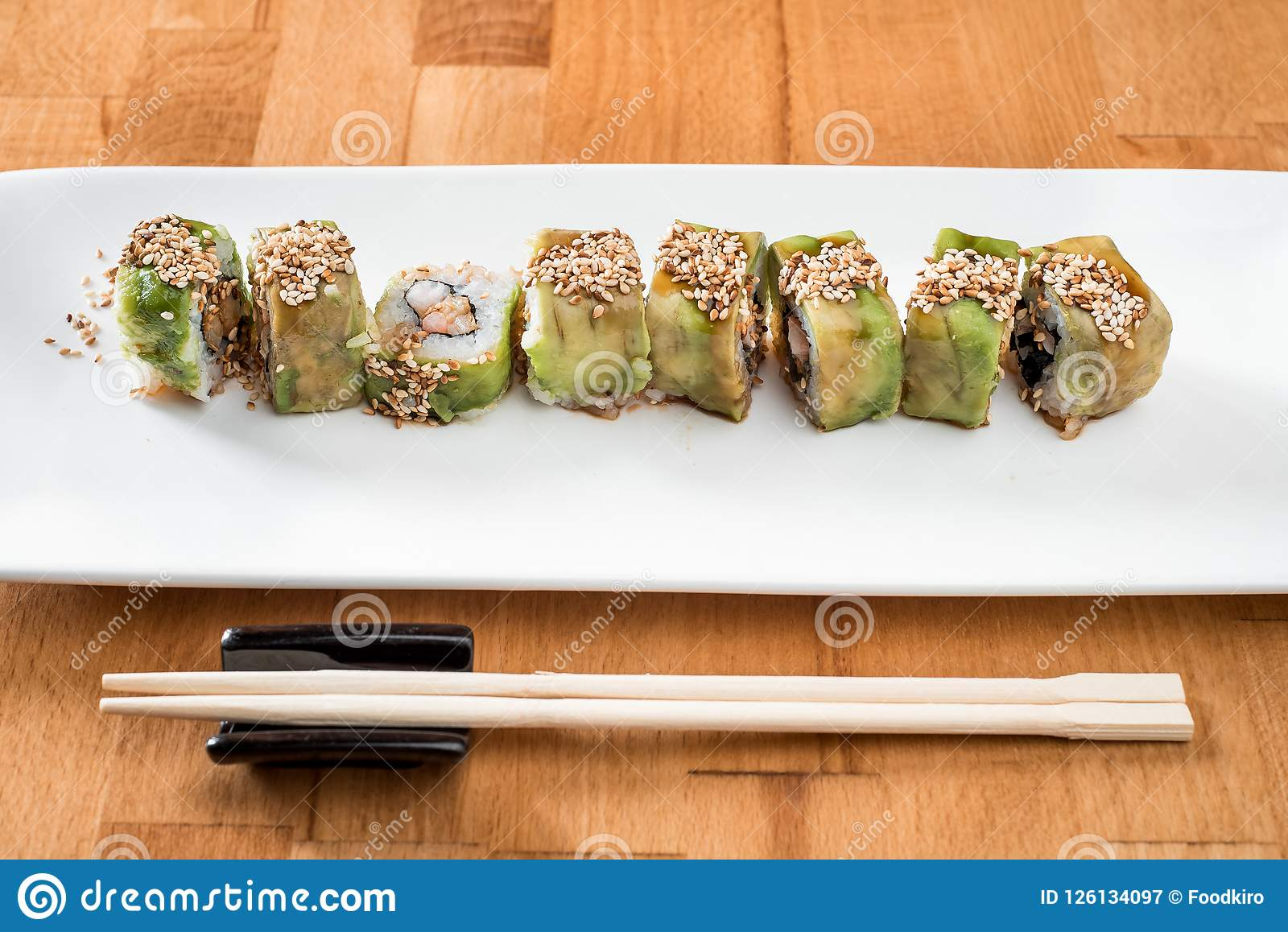 Japanese sushi roll green dragon with eel and avocado with ginger on a white plate. isolated. close up