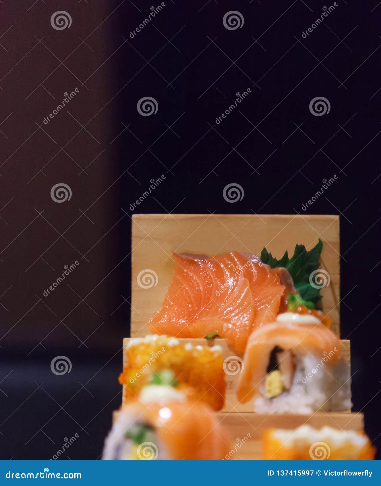 Japanische frische Fischfutter-Teller-Menü-, Salmon Sushi- und Sashimi-Zusammenstellung, die auf hölzernen Schritten auf traditio