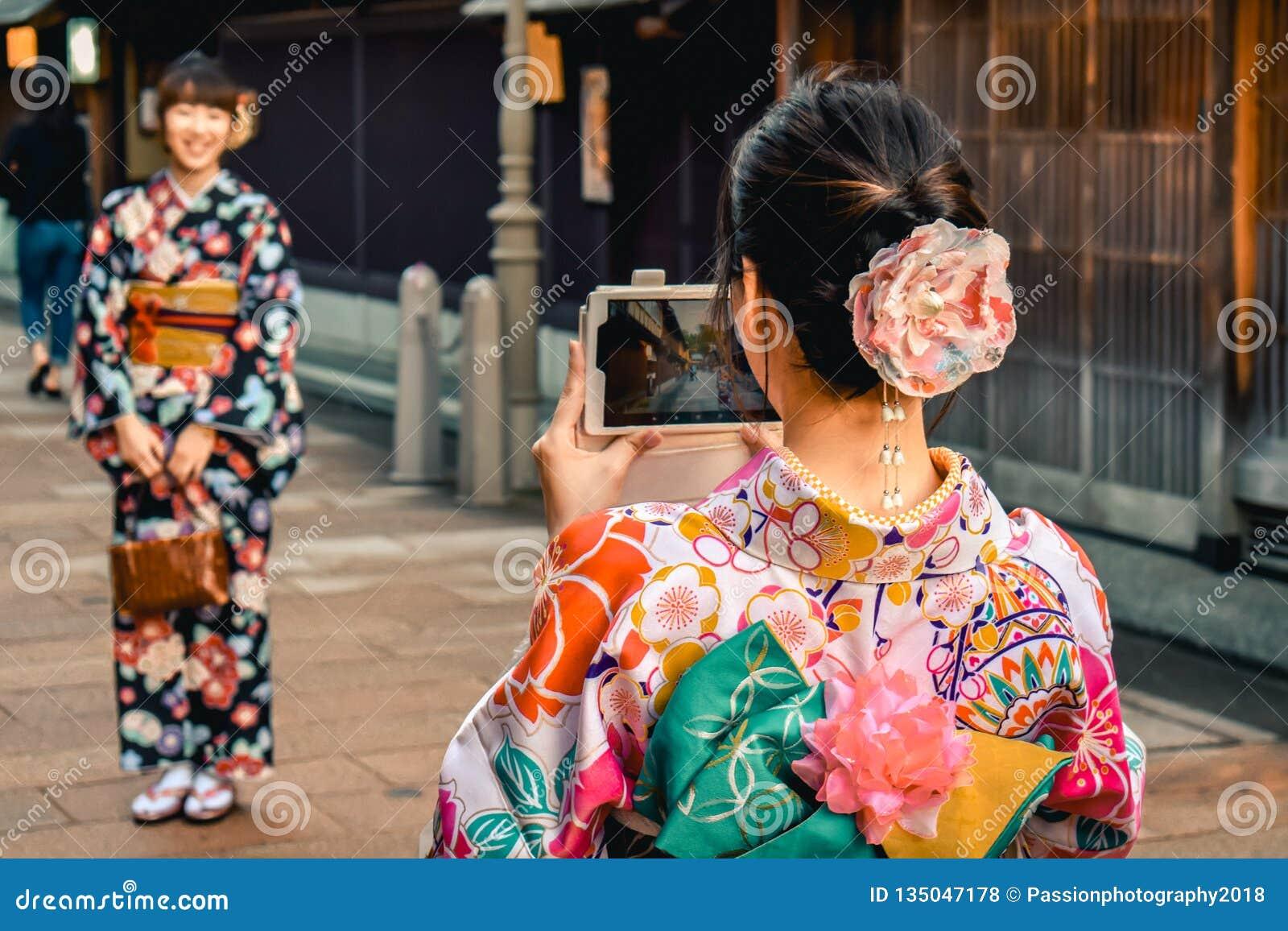 Japanische Mädchen in den nehmenden Fotos des Kimonos von einander an einem Handy in der alten Stadt Kanazawa