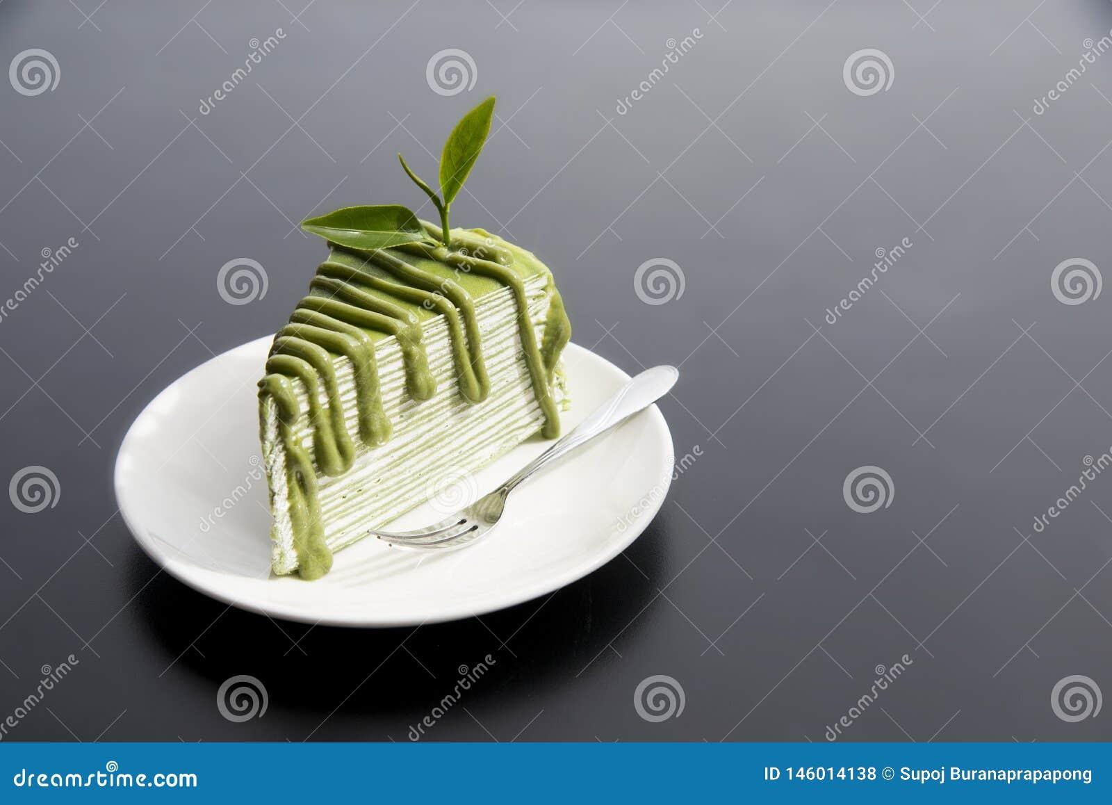 Japanischer Kuchen grünen Tees Matcha mit Teeblättern in der weißen Platte auf moderner schwarzer Tabelle im Hintergrund