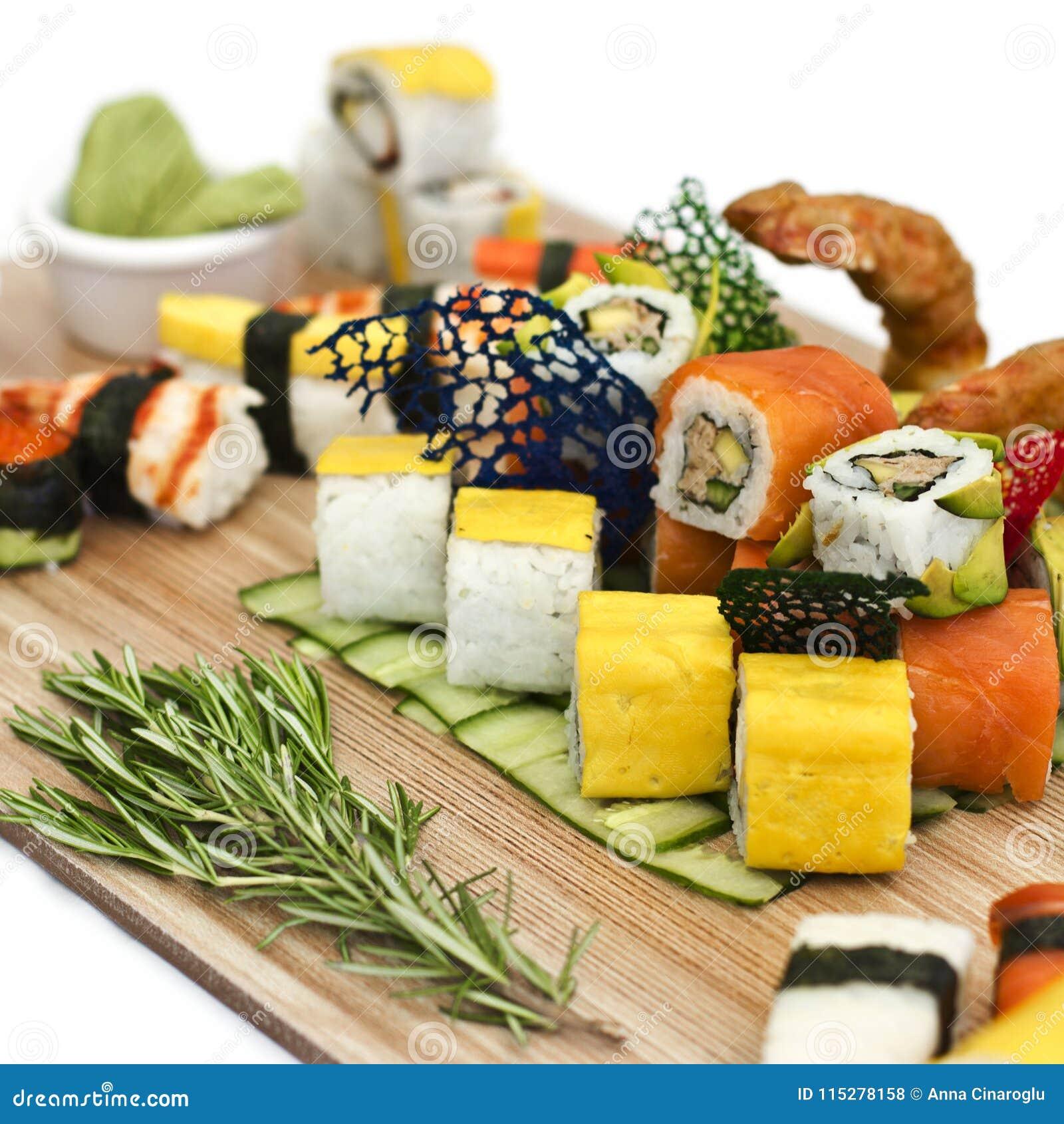 Japanisches Lebensmittel - Sushi, Sashimi, rollt auf einem hölzernen Brett isolat