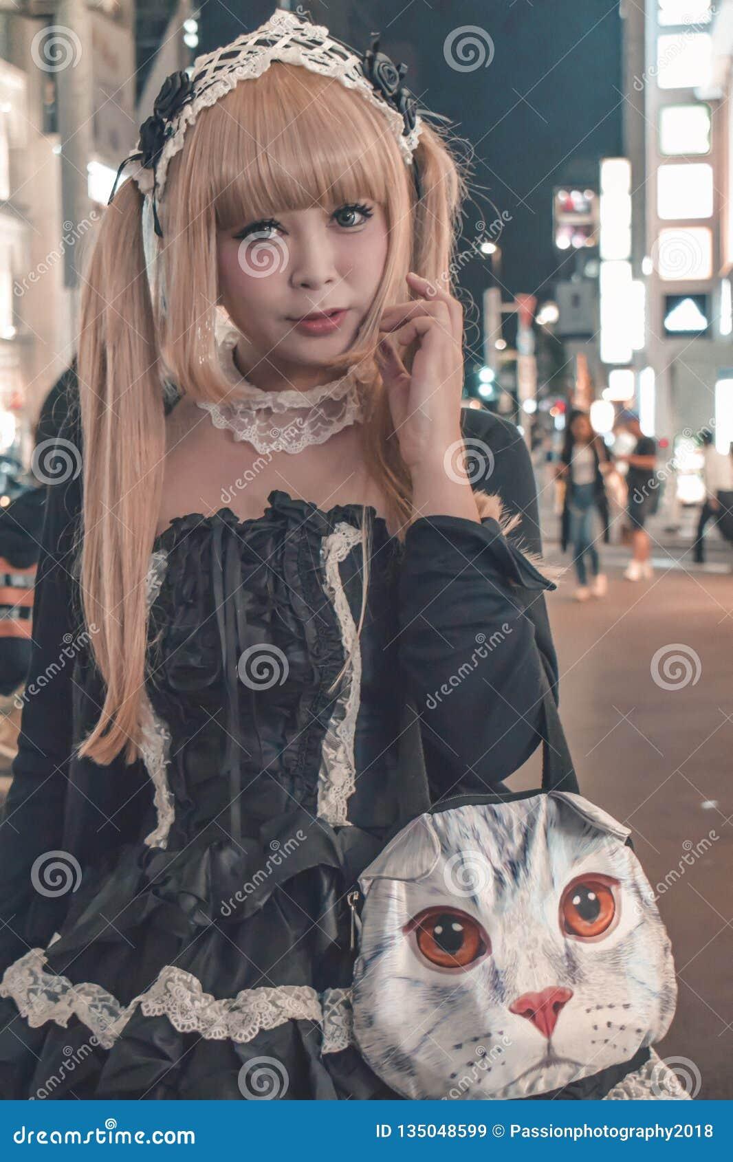 Japanisches Mädchen im schwarzen Kostüm und im blonden Tauchhaar gehend bei Harajuku in Beispiel Tokyos Japan des typischen Japan