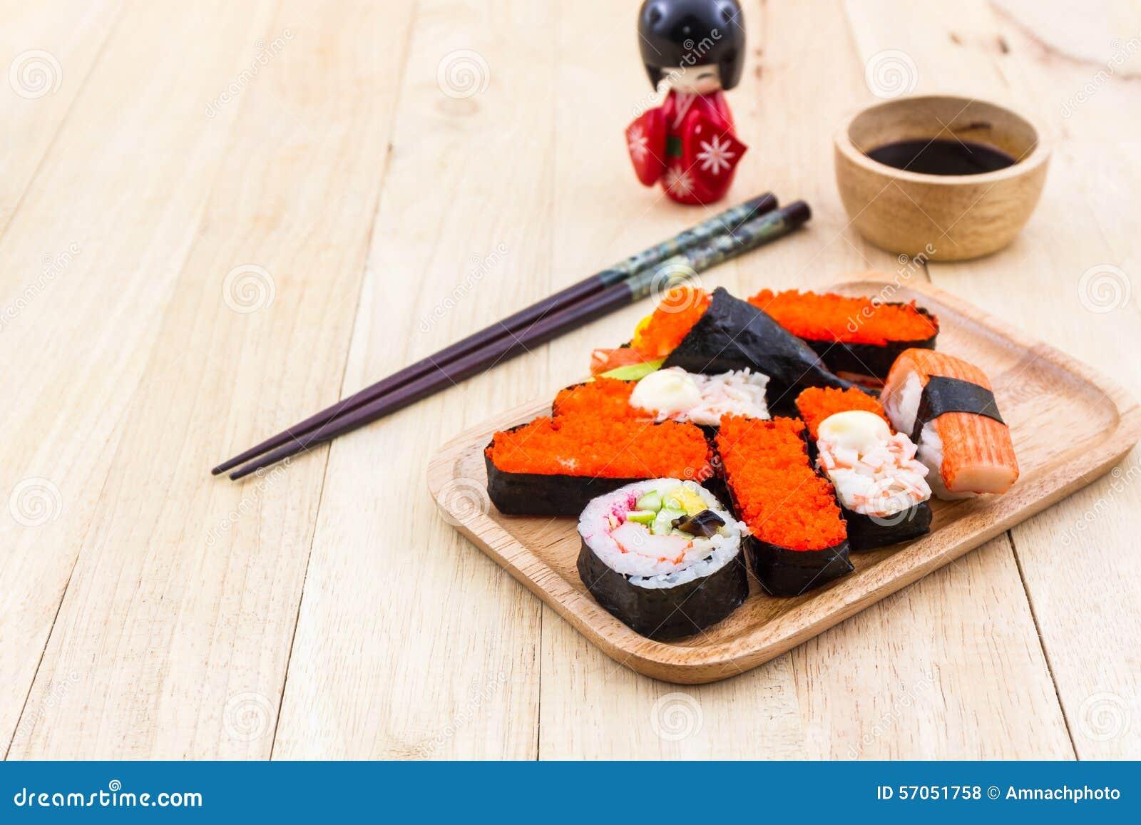 Japans sushi traditioneel voedsel op houten plaat met kokeshi