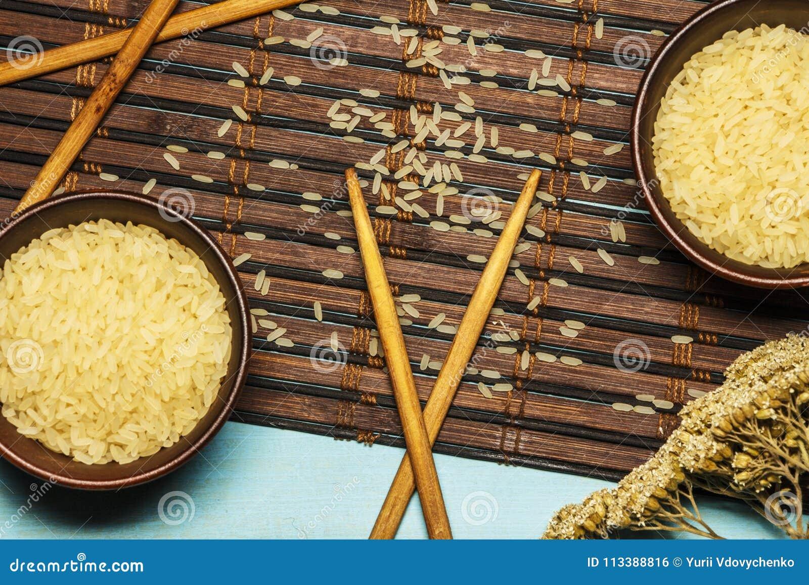 Japanse rijst in een houten kom Houten eetstokjes op de lijst van een bamboemat Aziatische keuken Mening van hierboven
