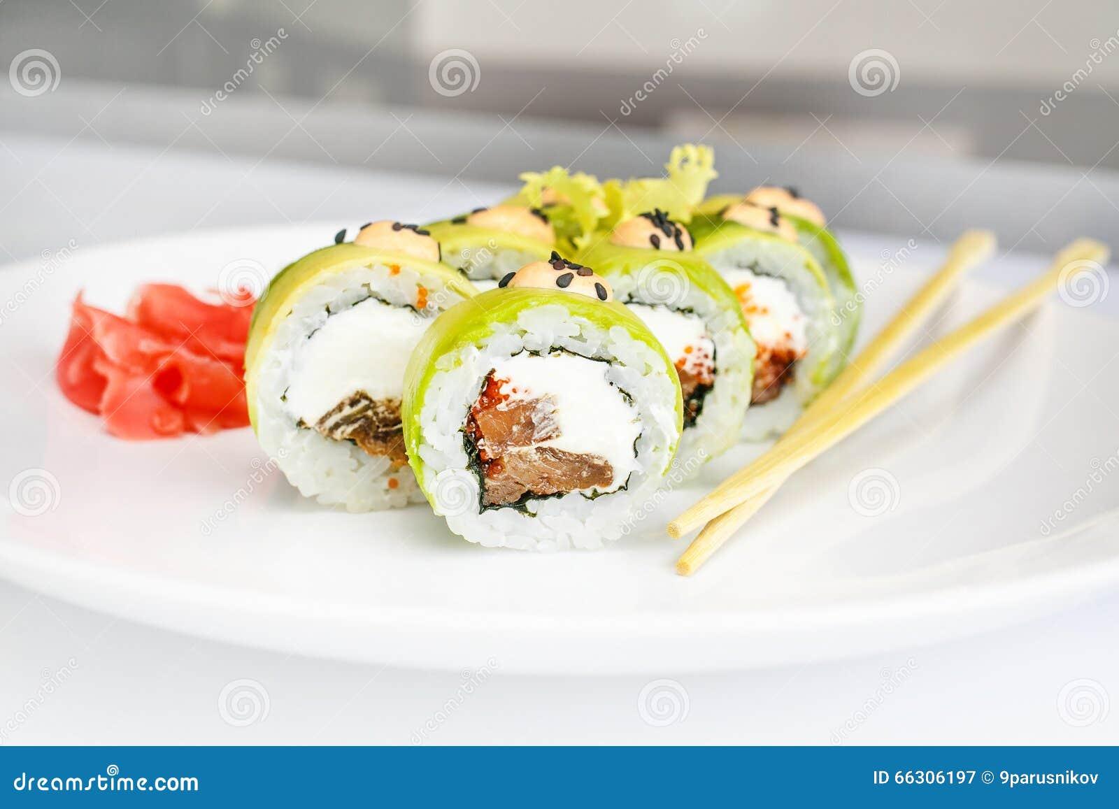 Japansk havs- sushi, rulle och pinne på en vit platta