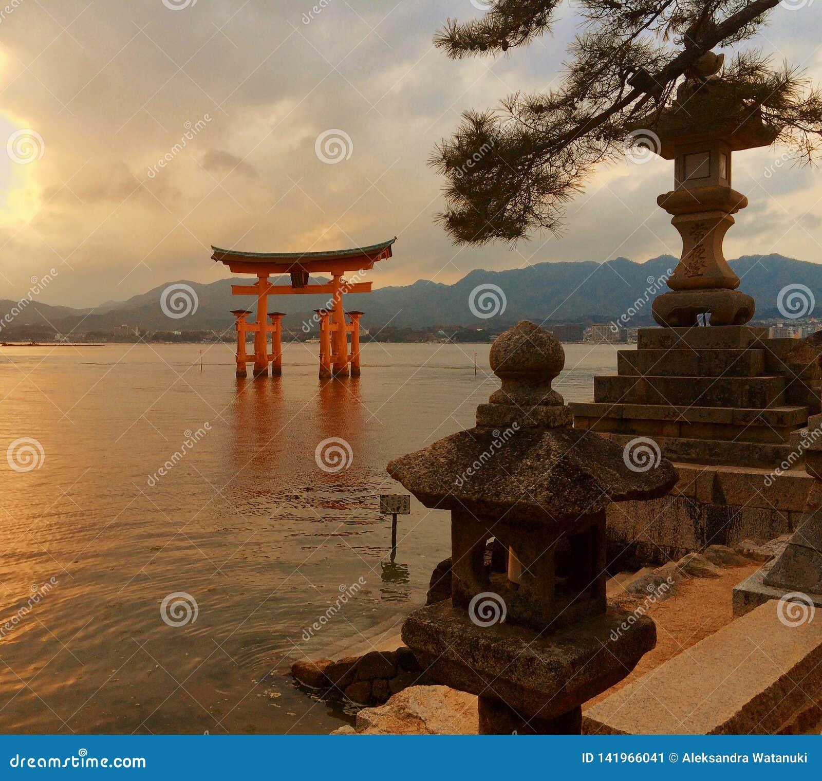 Japończyka Torii brama przy Miyajima przy zmierzchem